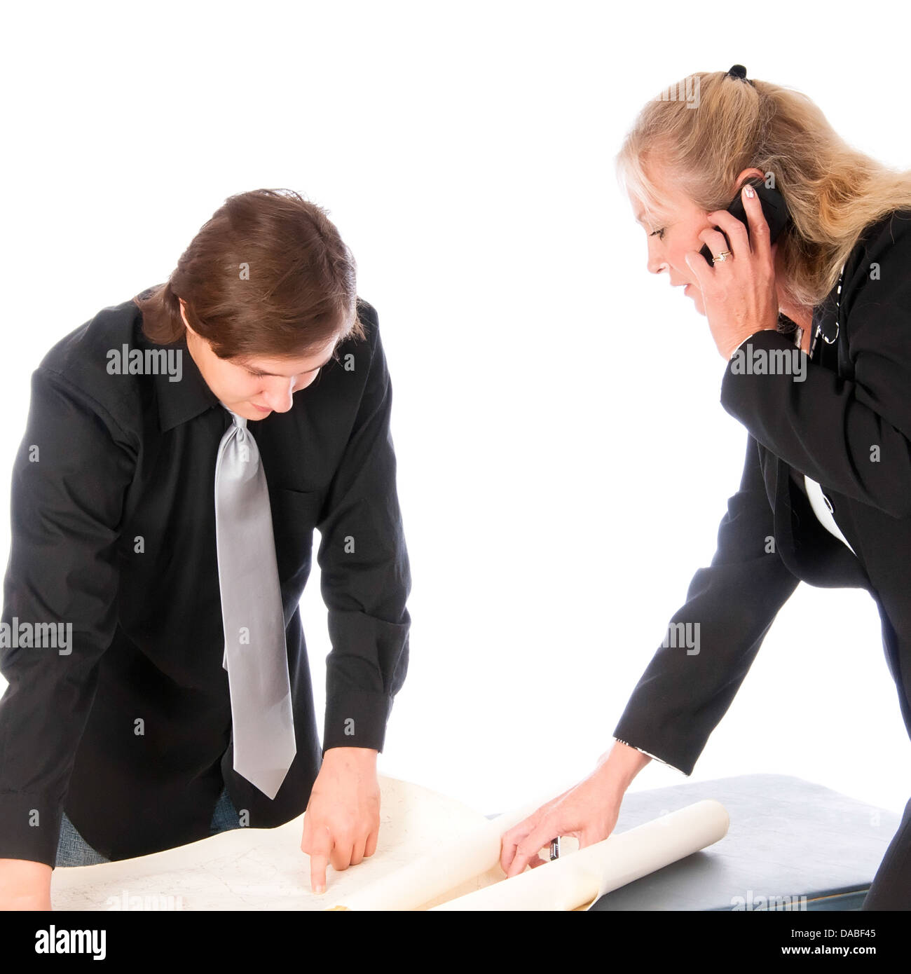 Woman manager shows a location on a topo map to a young colleague - Stock Image
