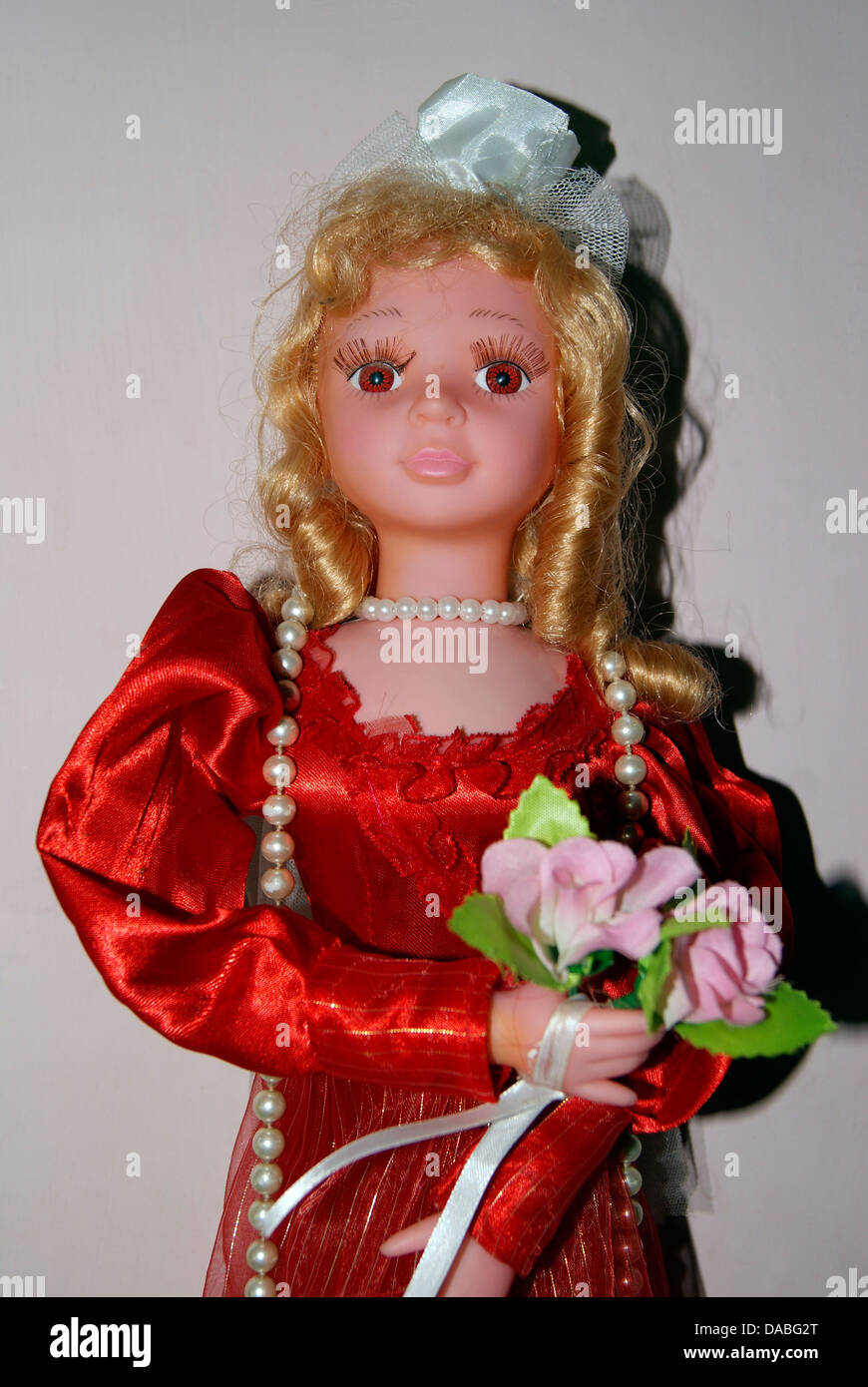 Beautiful Doll Girl Holding flowers - Stock Image
