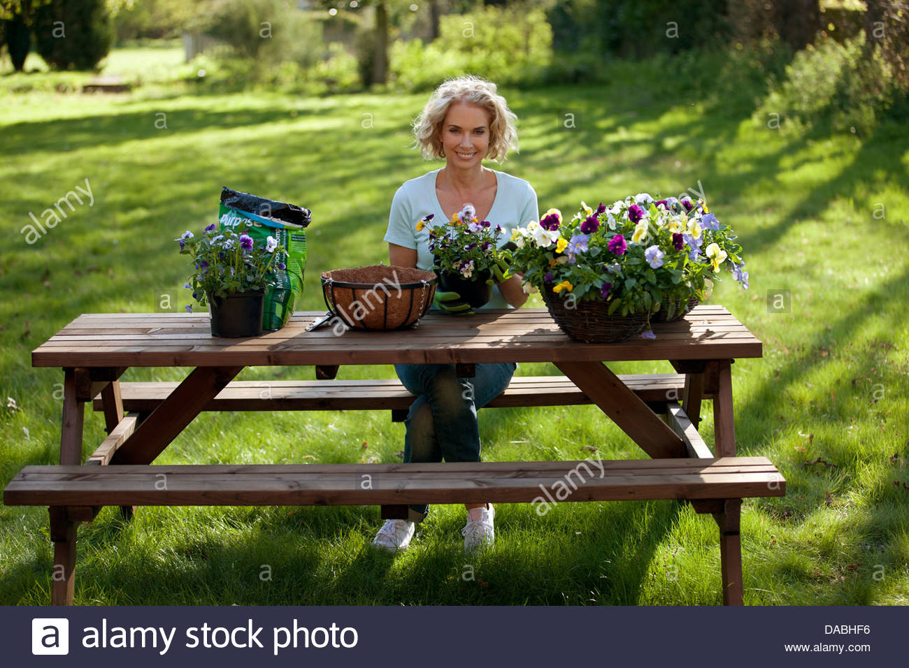 A mature woman sitting at a garden bench planting hanging baskets - Stock Image