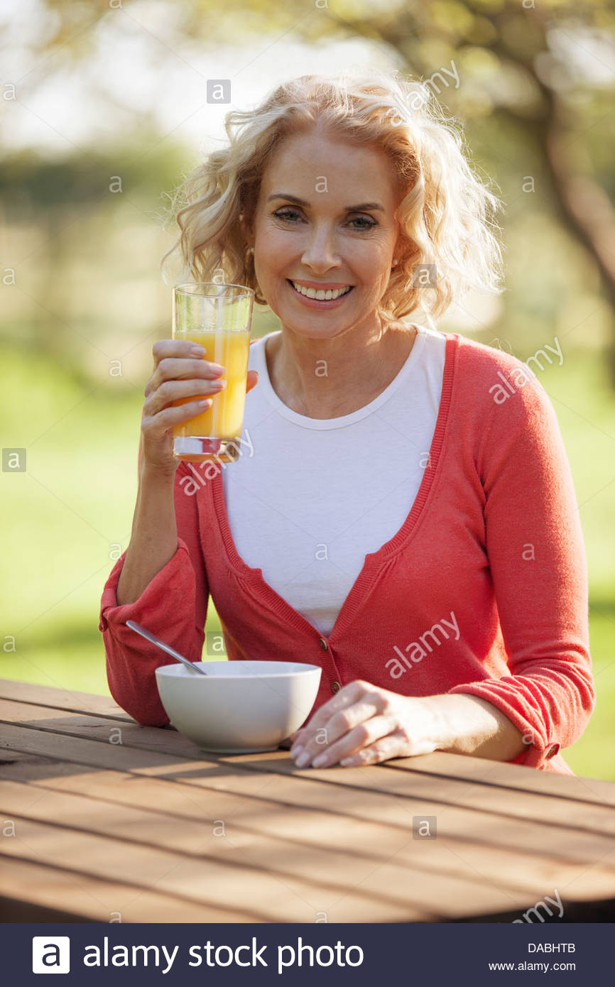 A mature woman sitting at a garden bench drinking orange juice - Stock Image