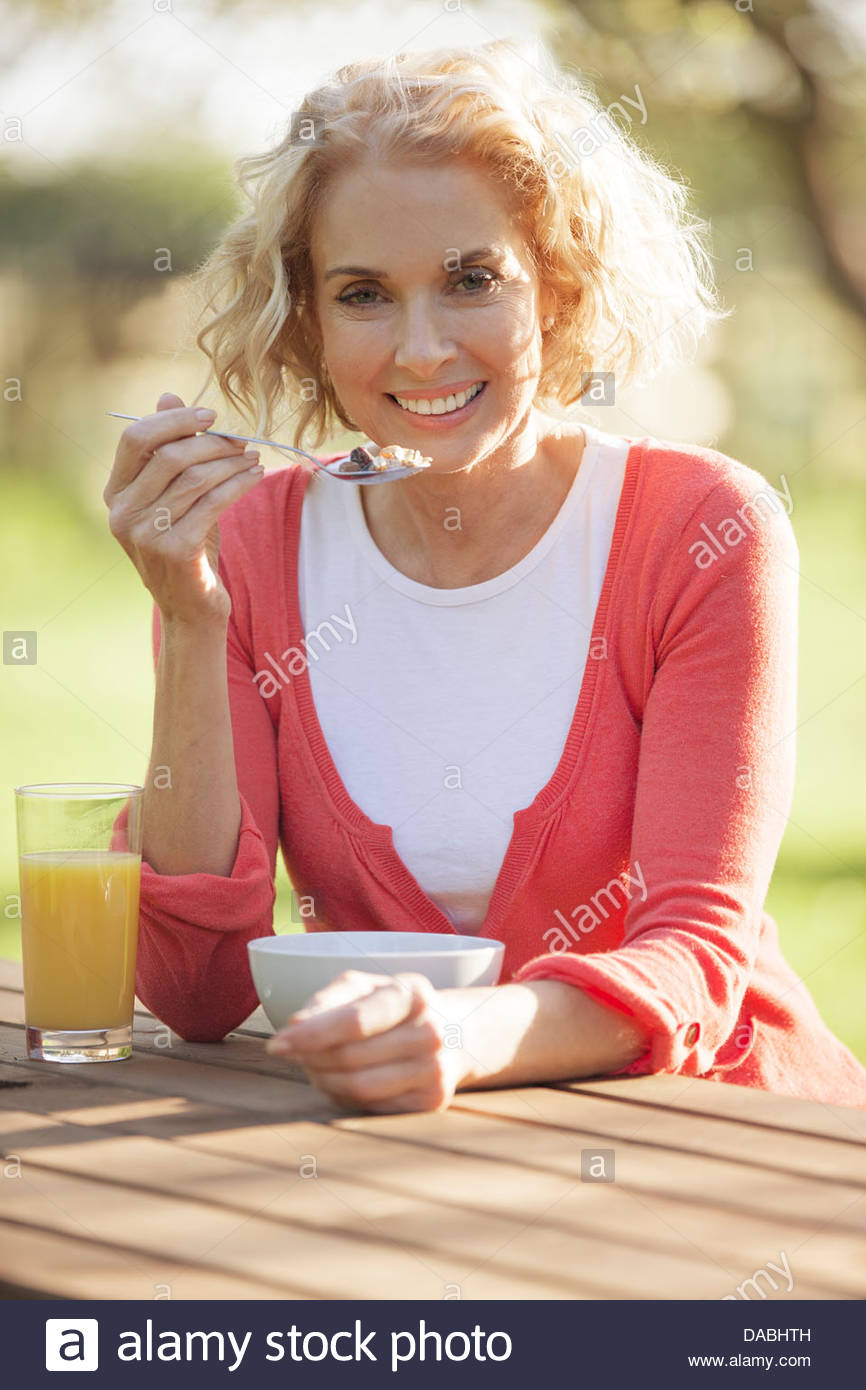 A mature woman sitting at a garden bench eating breakfast cereal - Stock Image