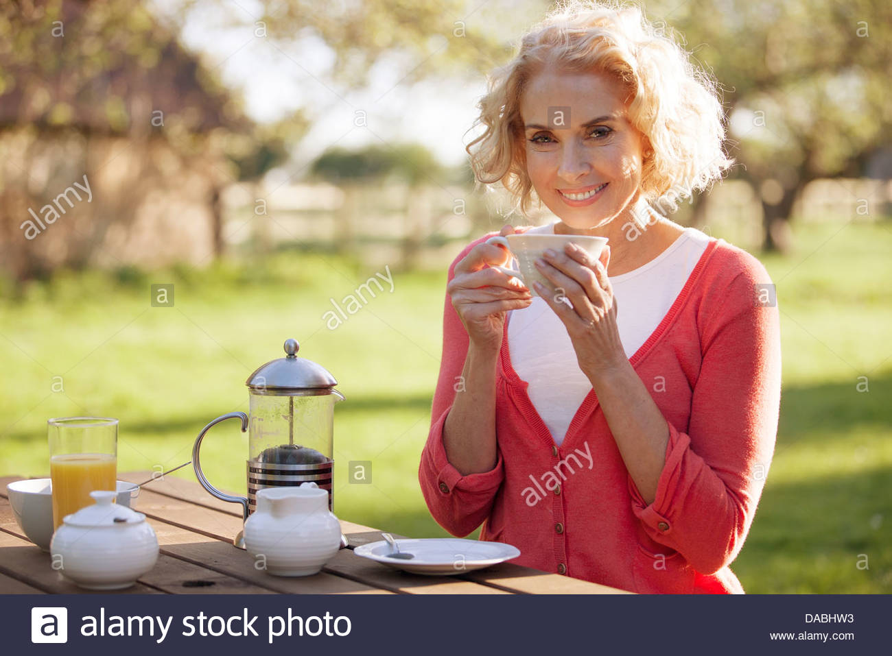A mature woman sitting at a garden bench drinking coffee - Stock Image