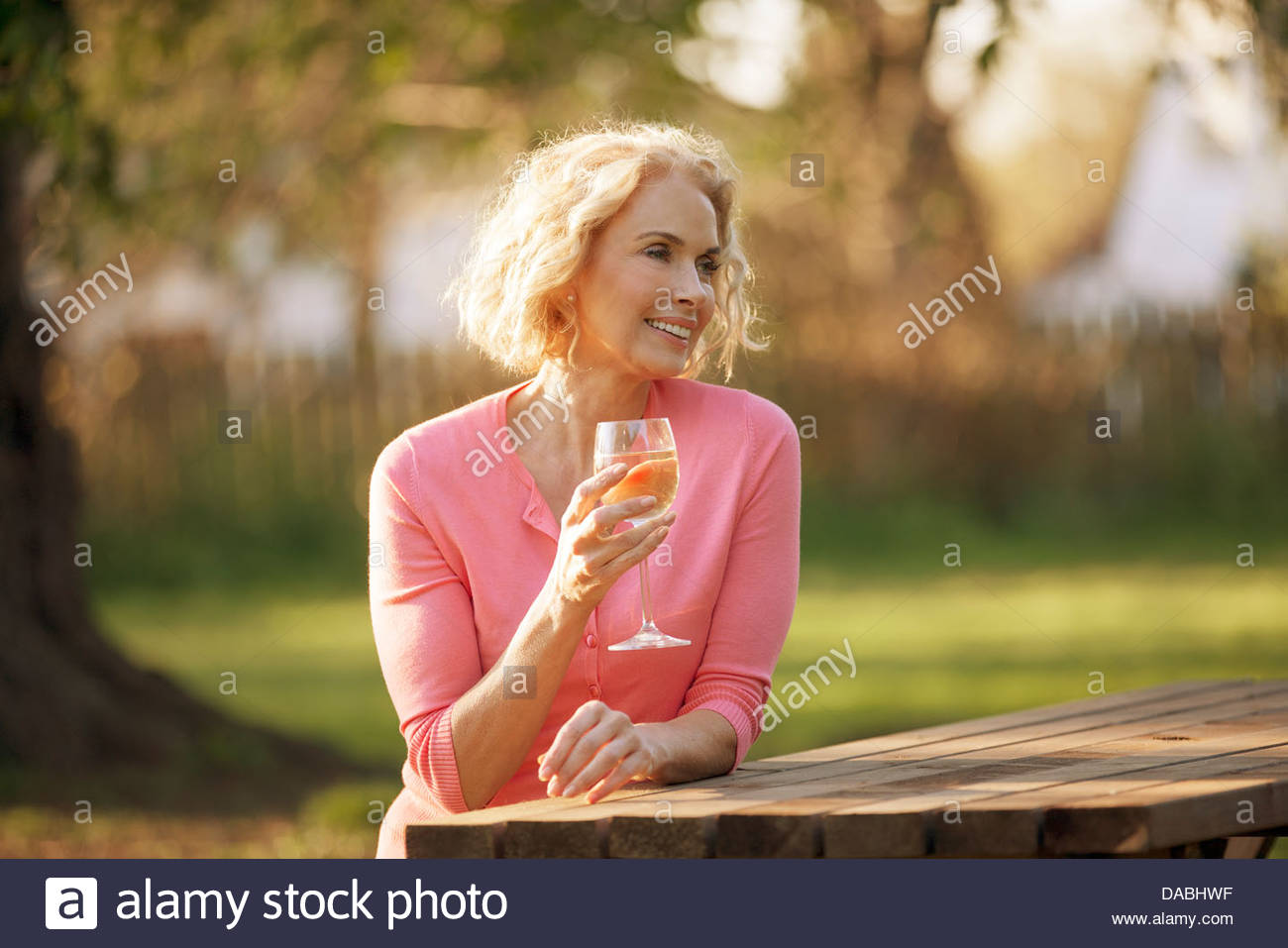 A mature woman sitting at a garden bench drinking a glass of wine - Stock Image
