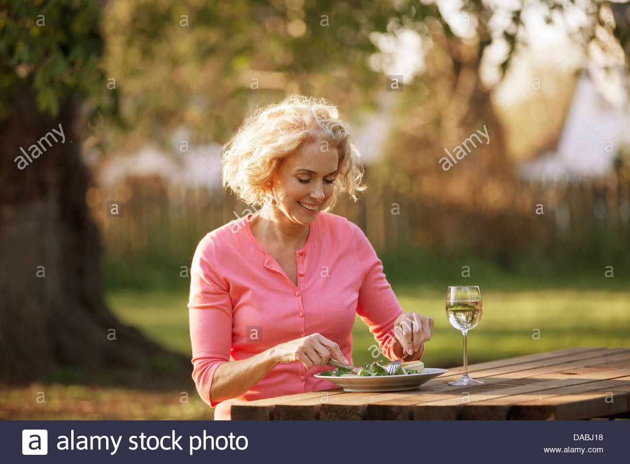 A mature woman sitting at a garden bench eating a meal - Stock Image