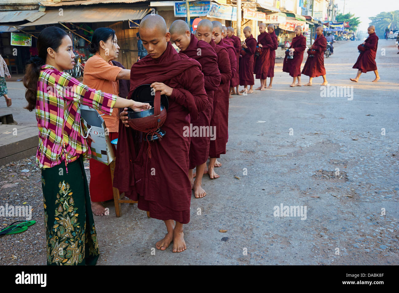 Buddhist monks procession receive offerings, Mawlamyine (Moulmein), Mon State, Myanmar (Burma), Asia - Stock Image
