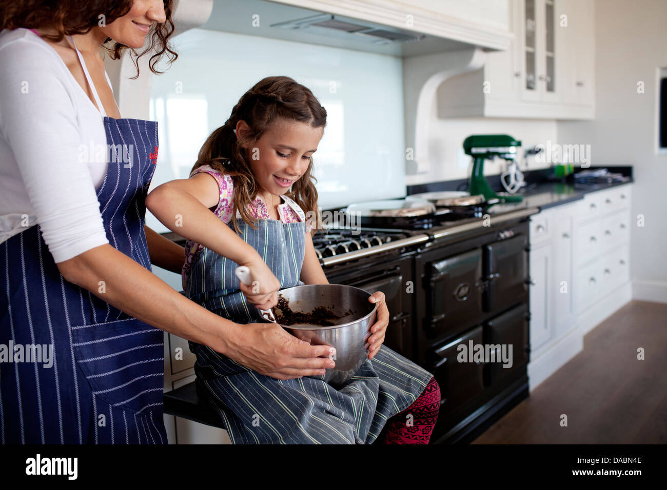 Young girl mixes cake mix in bowl as mother holds bowl to steady it in kitchen next to an aga stove - Stonehurst - Stock Image