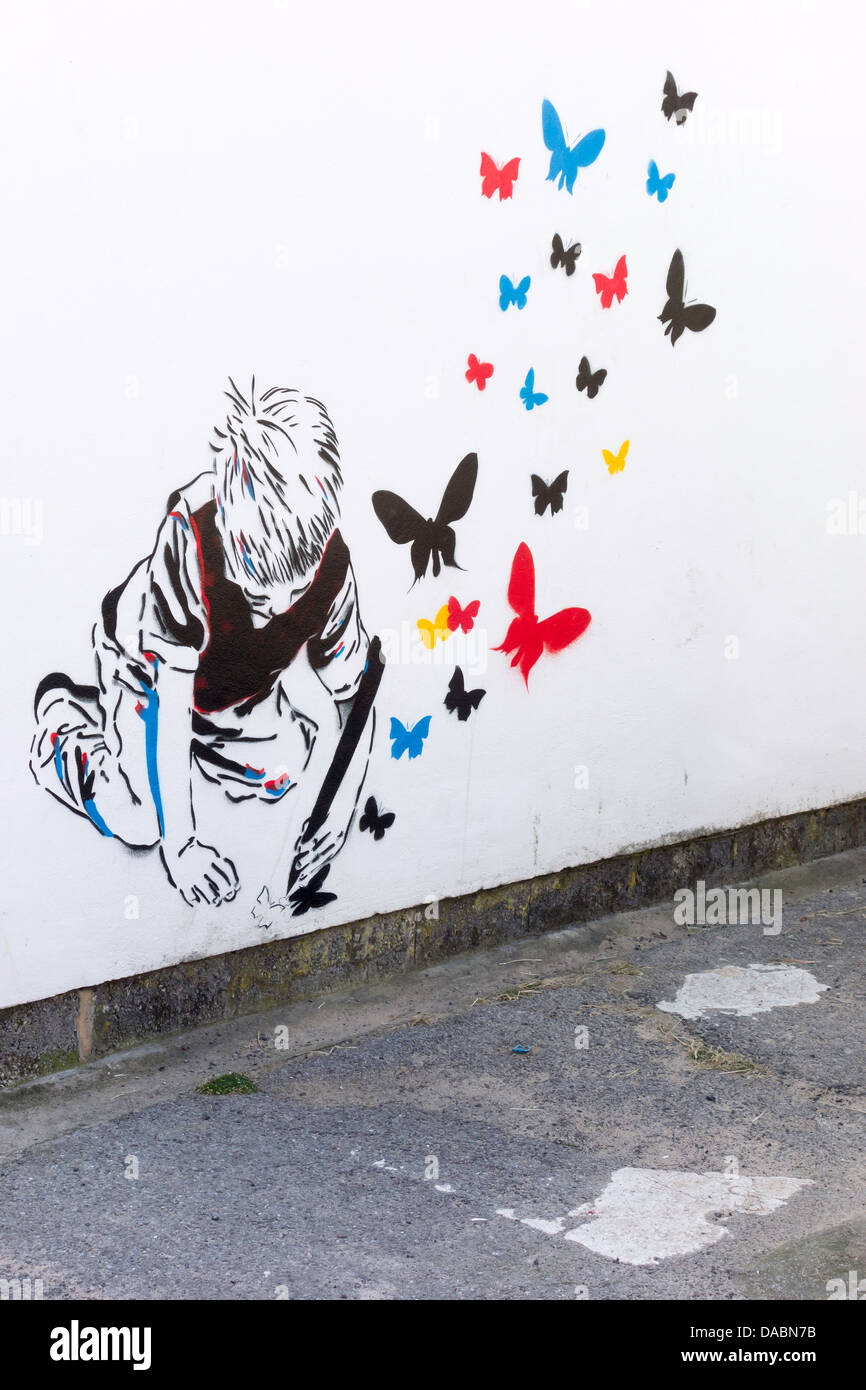 A Graffito of a boy drawing butterflies which are flying away - Stock Image
