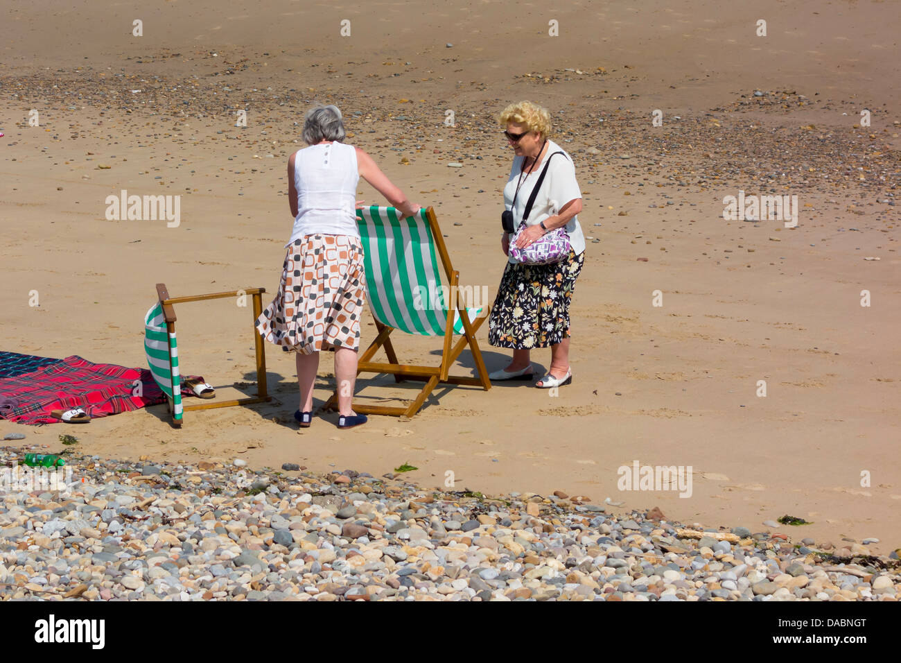 Two ladies on an English beach setting up their hired deck chairs on a hot summeru0027s day & Two ladies on an English beach setting up their hired deck chairs on ...