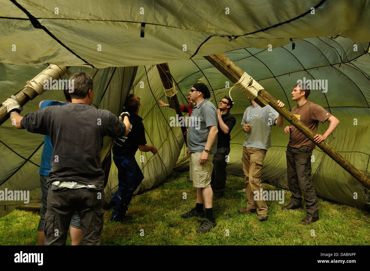 Teamwork excercise putting up a tent - Stock Image