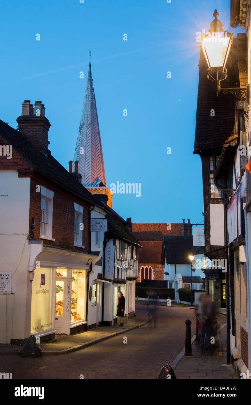 The spire of parish church stands at dusk above a historic street in Godalming, Surrey, England, United Kingdom, - Stock Image