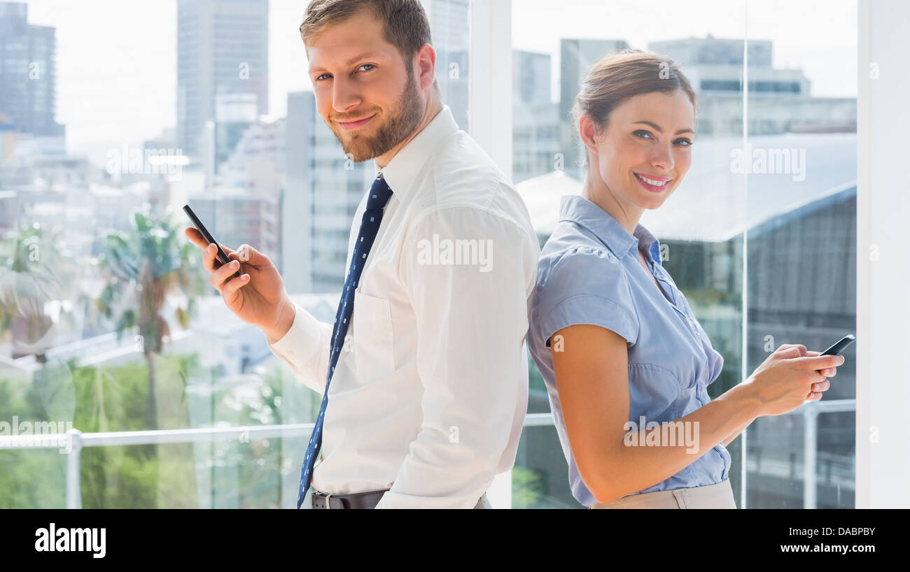 Smiling business team standing back to back and texting - Stock Image