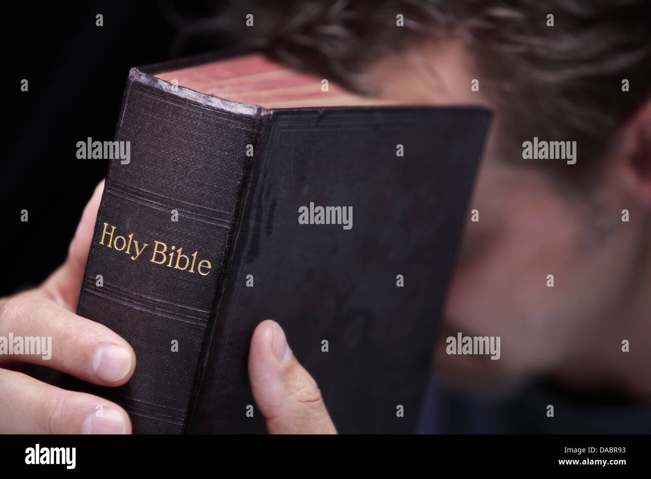 Hands clasped in prayer around Holy Bible - Stock Image