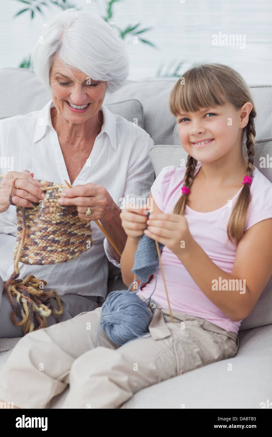 Portrait of a little girl and her granddaughter knitting together - Stock Image