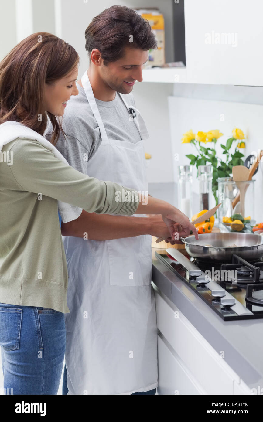 Delighted couple cooking - Stock Image