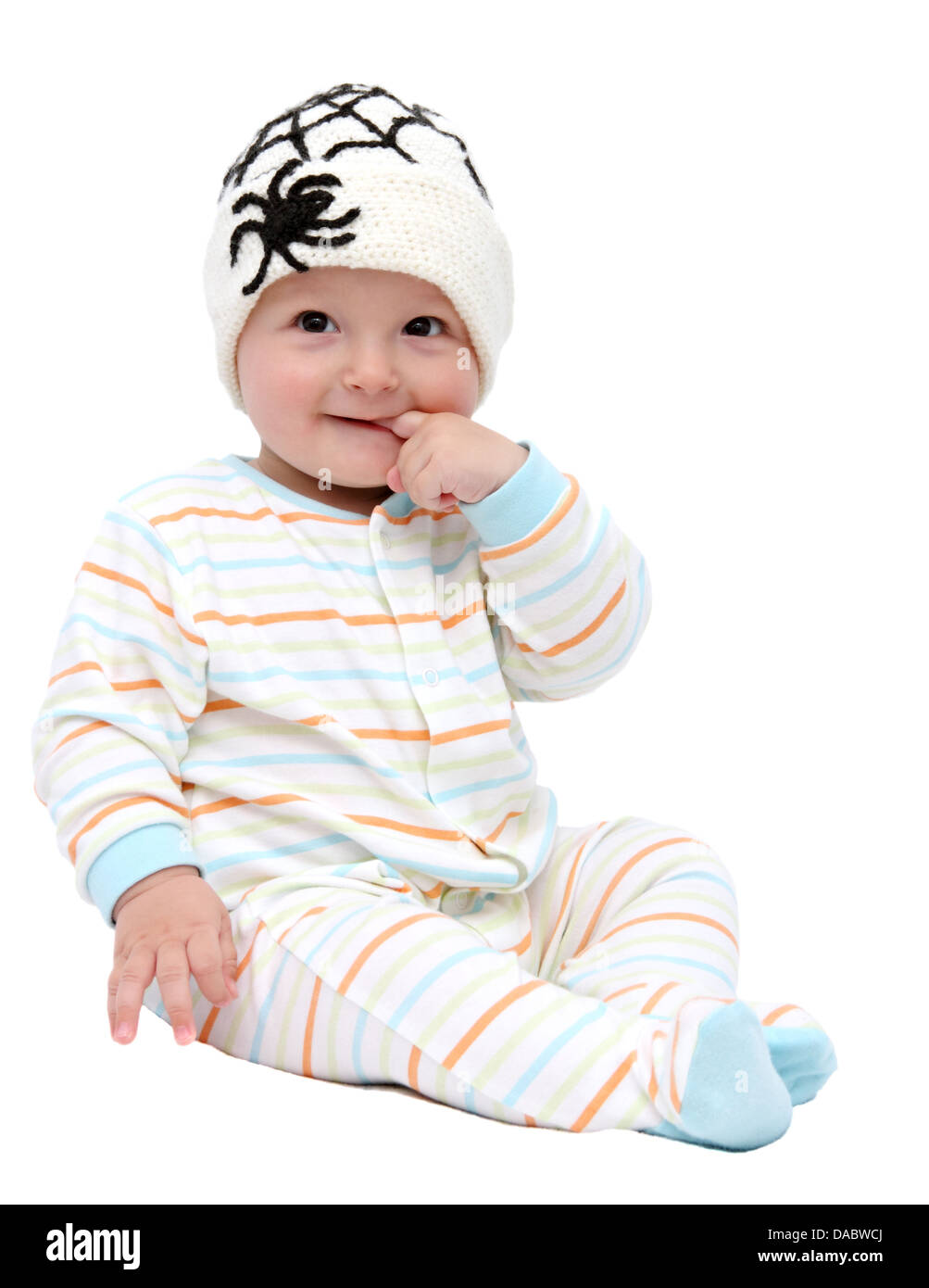 beautiful baby boy with knitted hat sitting - Stock Image