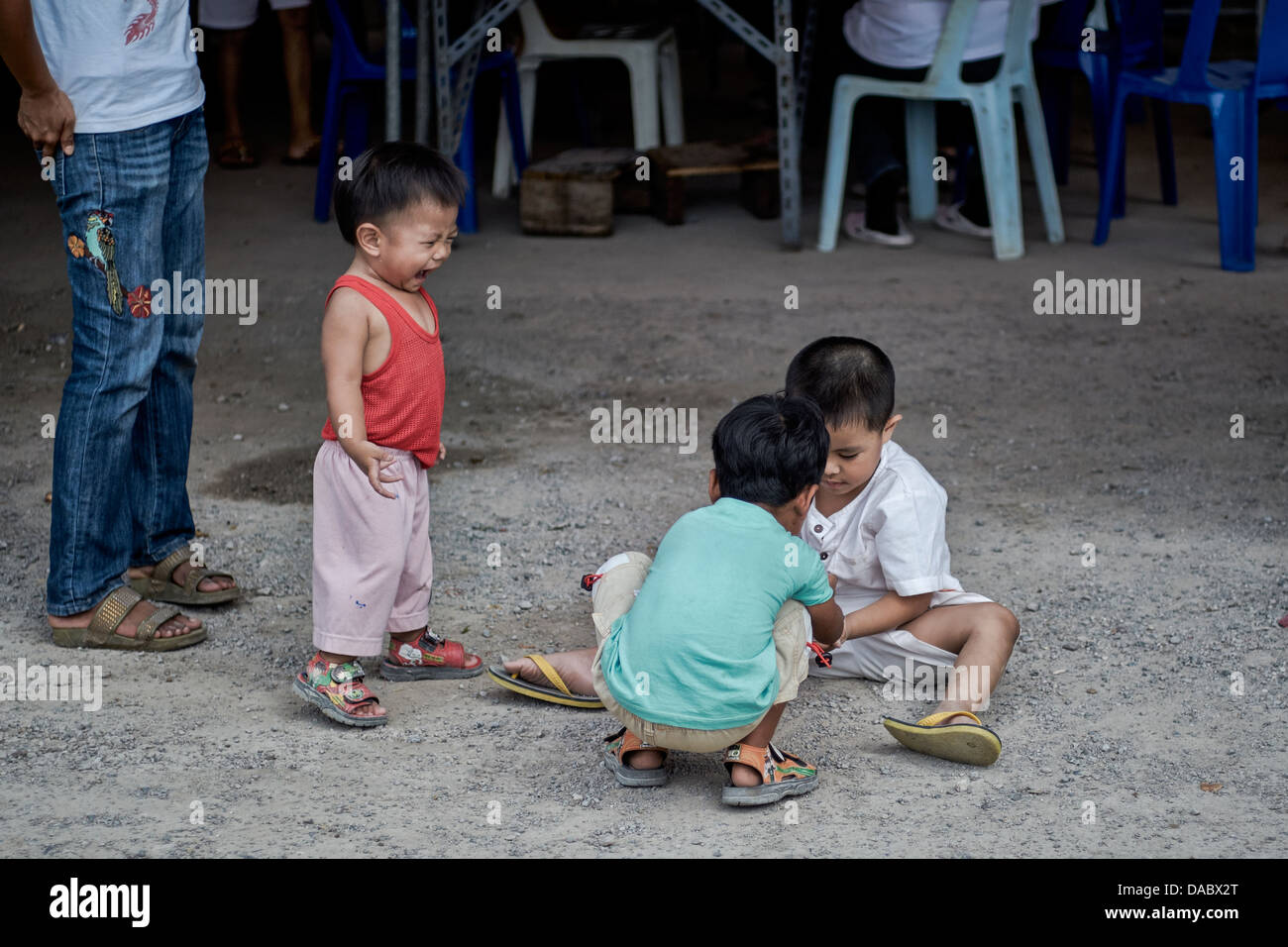 Amusing image of an irate and angry child showing his frustration when not involved in friends games. Thailand S. - Stock Image