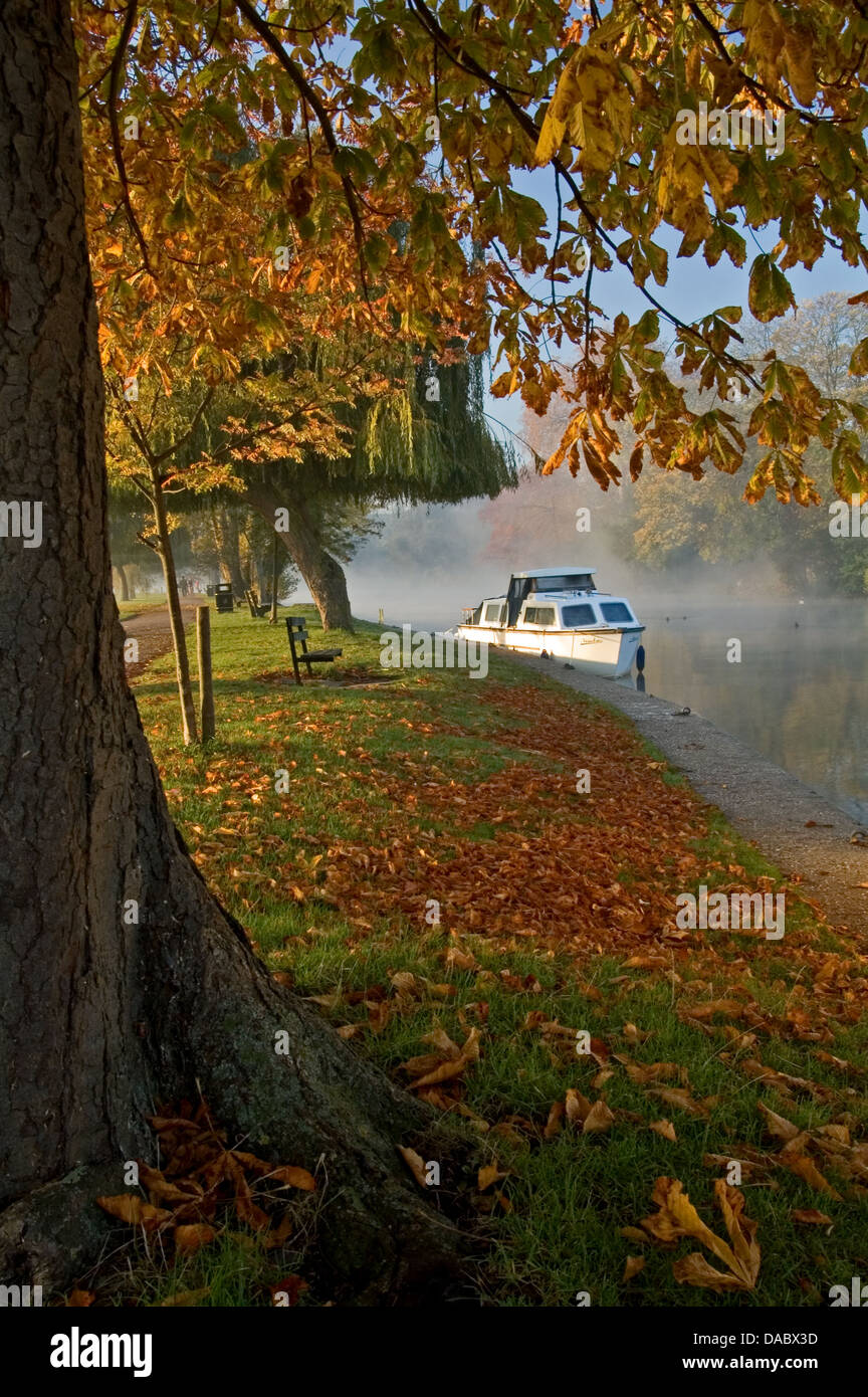 Stratford upon Avon, Warwickshire and a white motor cruiser moored on the River Avon on a misty autumn morning. - Stock Image