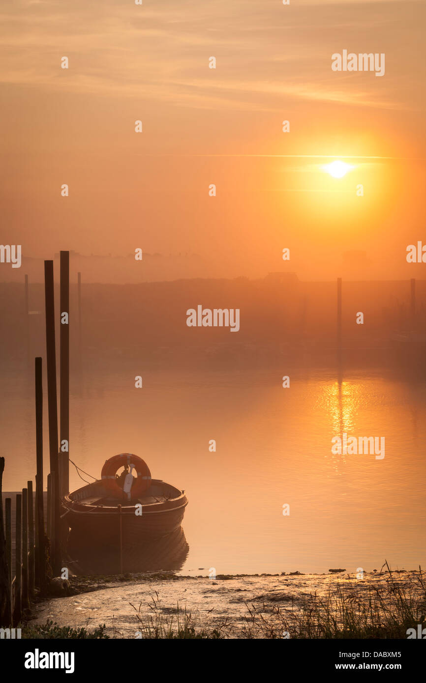 The sun burns off the early morning mist over the small Suffolk harbour at Blackshore, Walberswick. - Stock Image