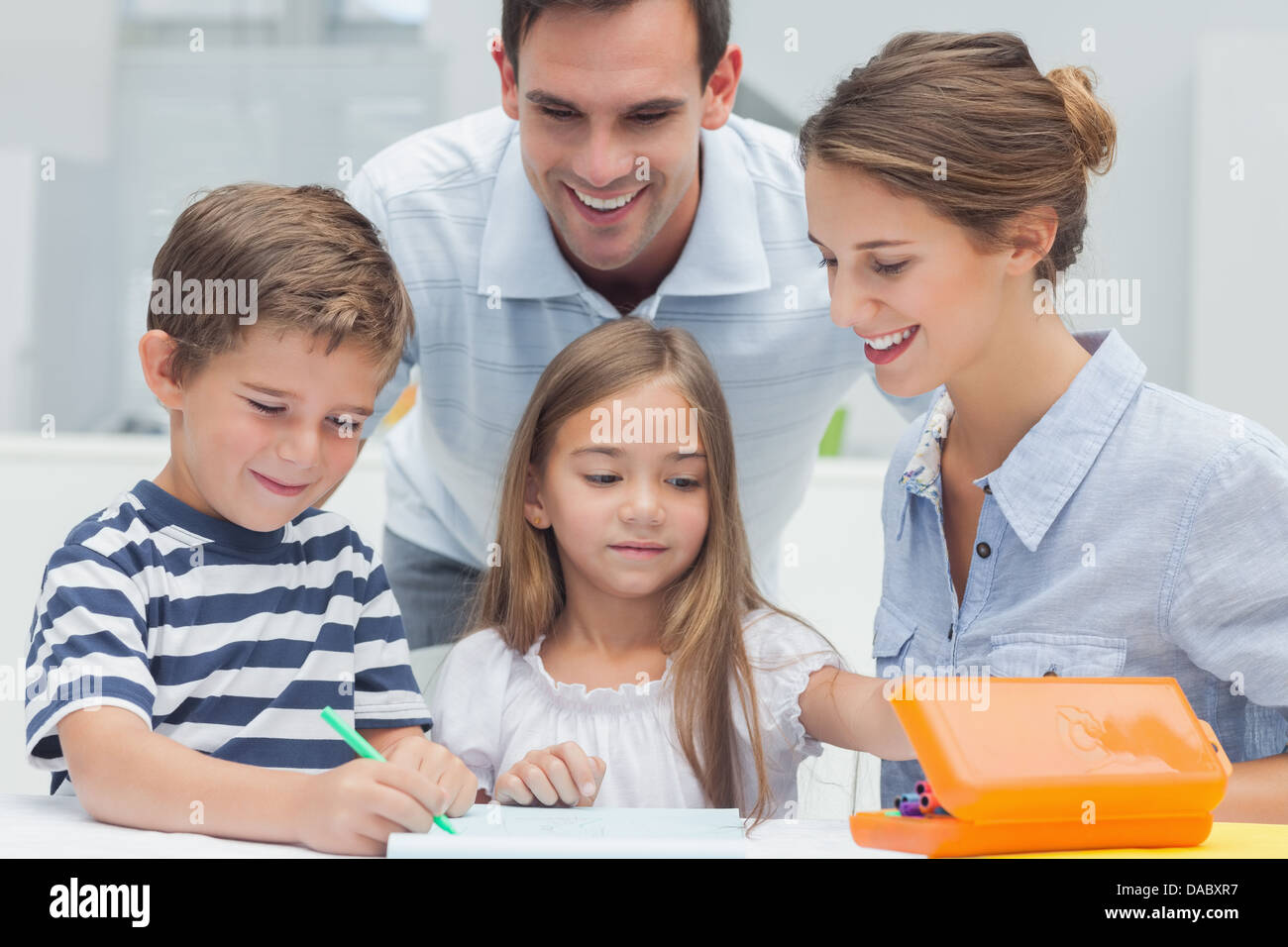 Parents looking at their children drawing - Stock Image