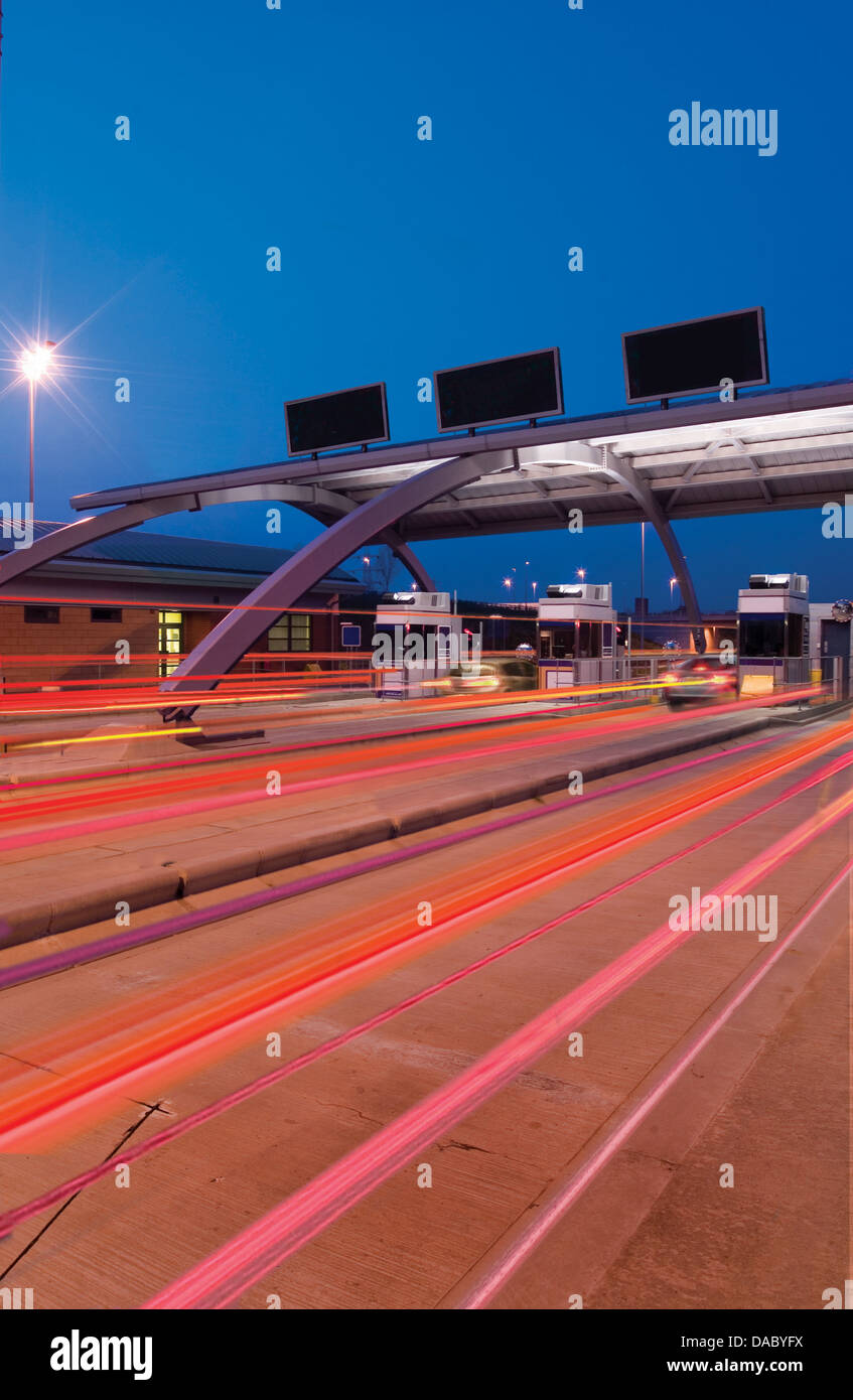 Toll booth with streaming lights and signs at night - Stock Image