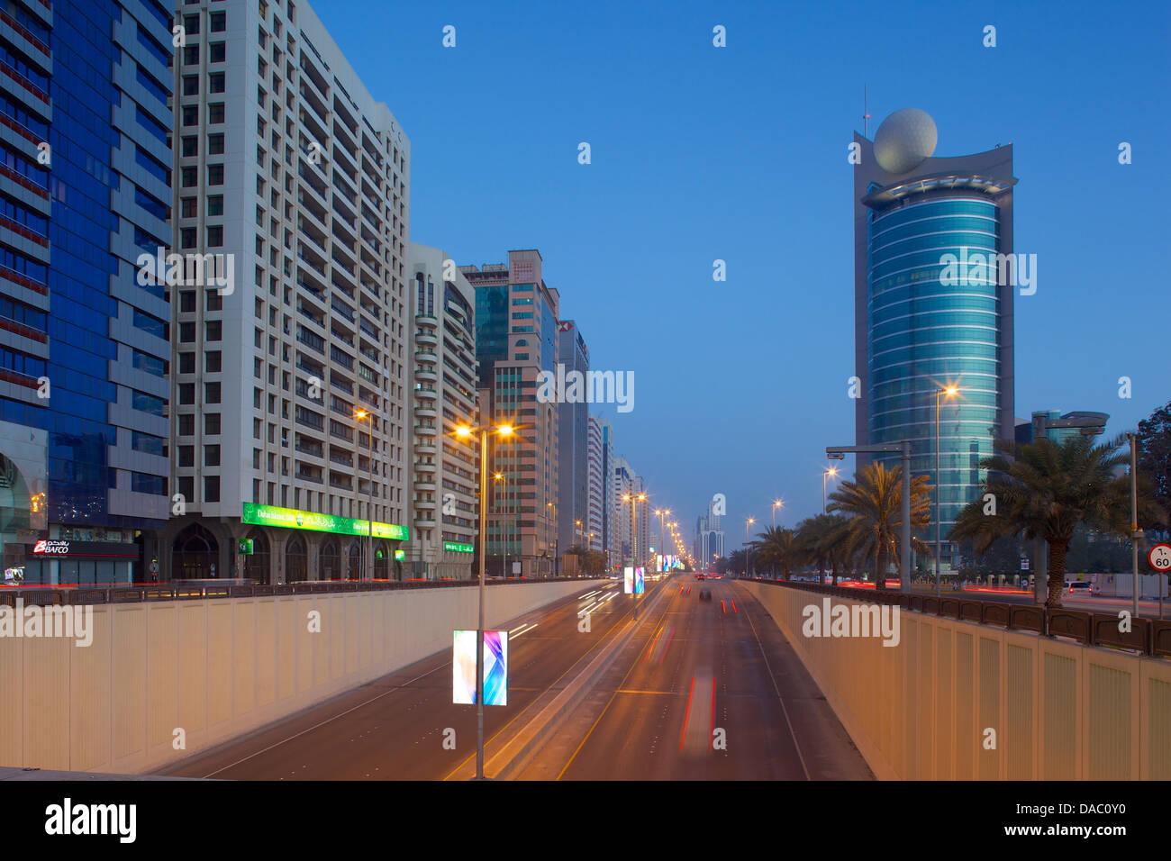 City skyline on Rashid Bin Saeed Al Maktoum Street at dusk, Abu Dhabi, United Arab Emirates, Middle East - Stock Image