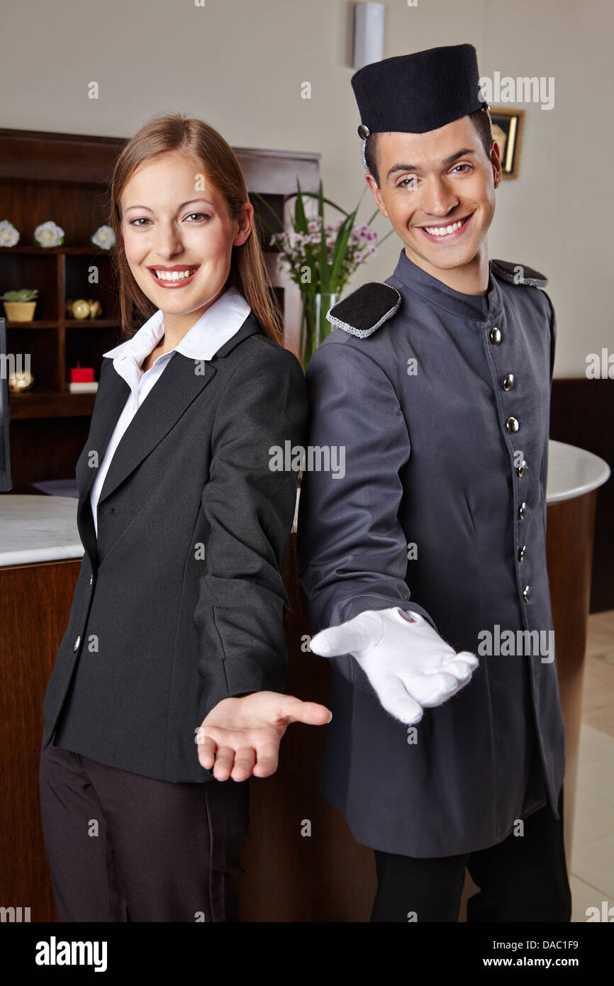 Smiling receptionist and happy bellboy in hotel offering a welcome - Stock Image