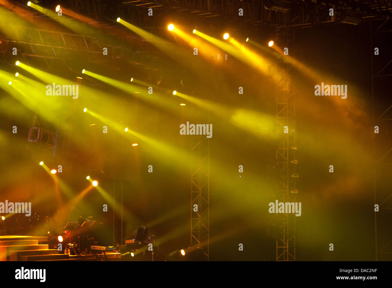 Image of yellow stage lights, thick fog creates drama - Stock Image
