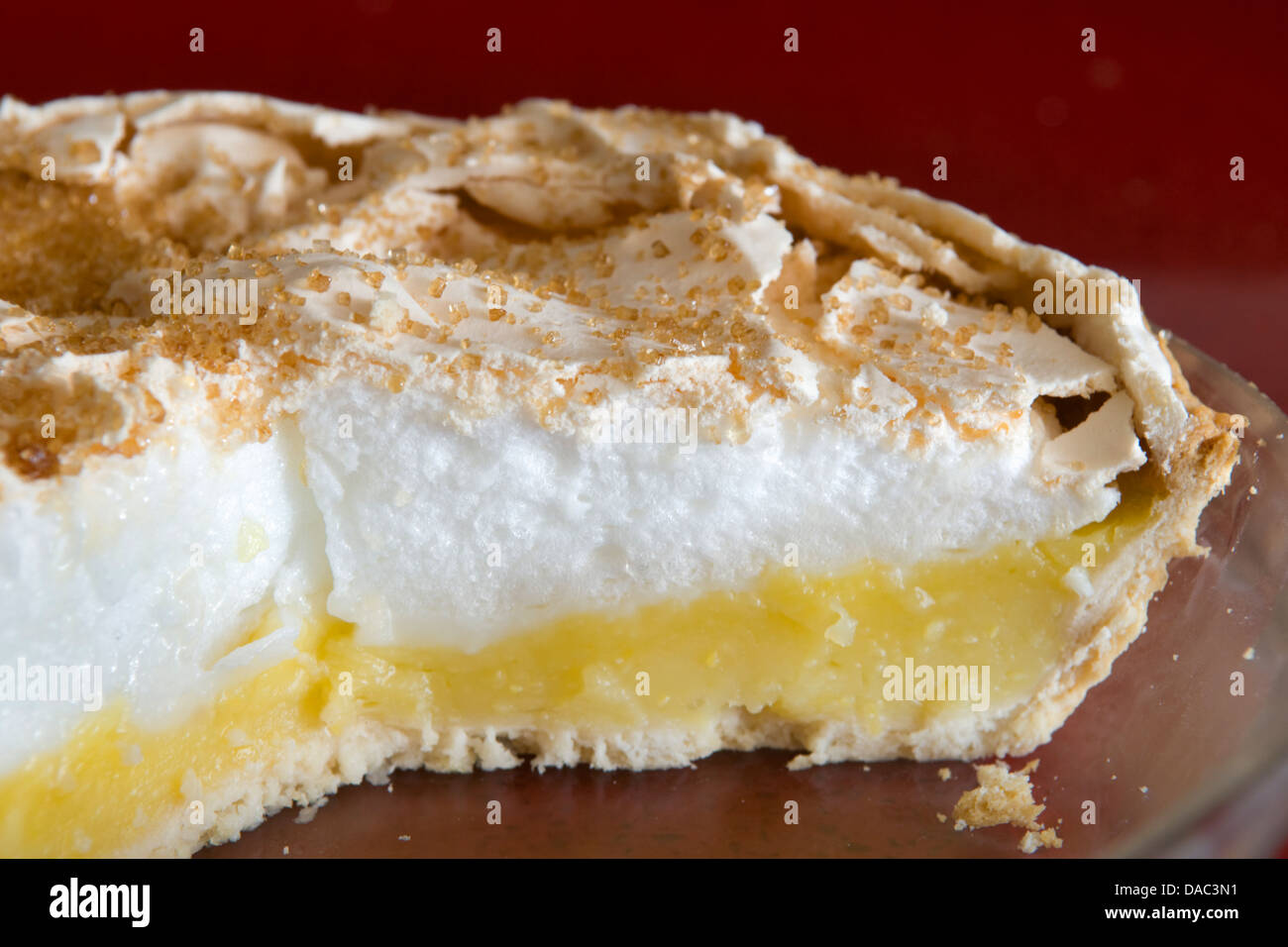 Home made lemon meringue pie in glass bowl on red worktop - Stock Image