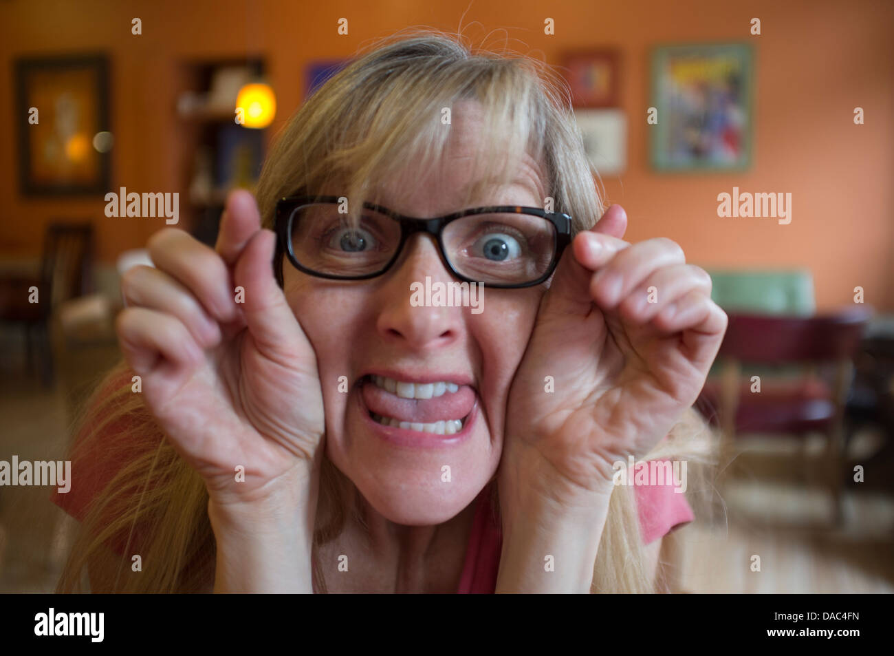 Closeup of woman looking at camera with silly expression- holding hands by face, eyes wide open and tongue stuck - Stock Image