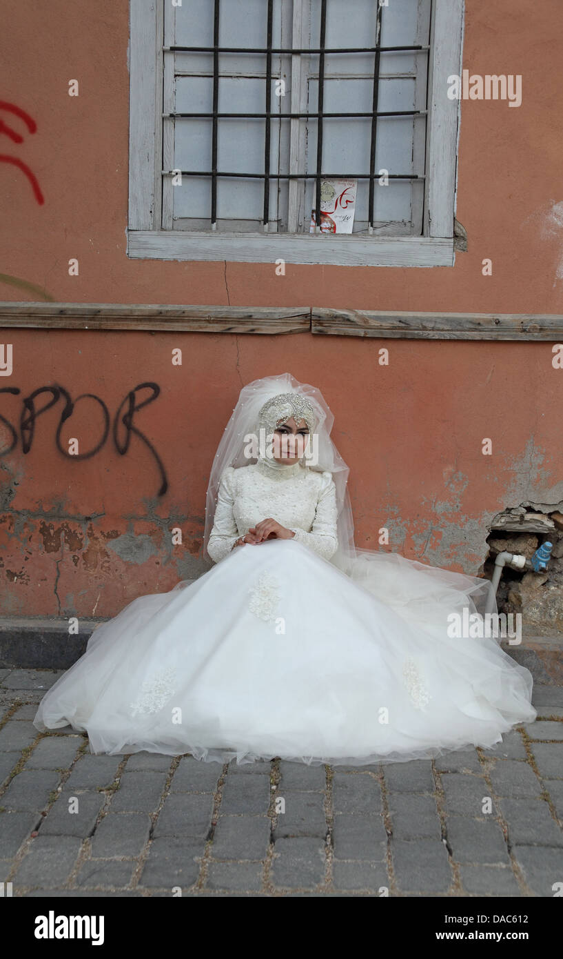A Muslim bride sits waiting in a dirty backstreet in Antalya Turkey - Stock Image