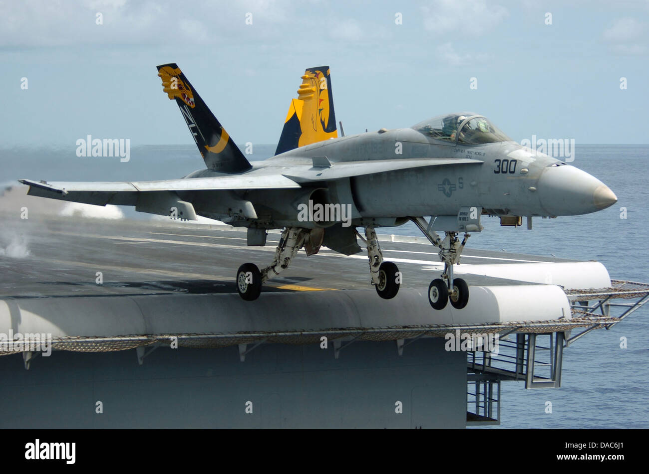 An F-A-18C Hornet launches from the flight deck of the conventionally powered aircraft carrier - Stock Image