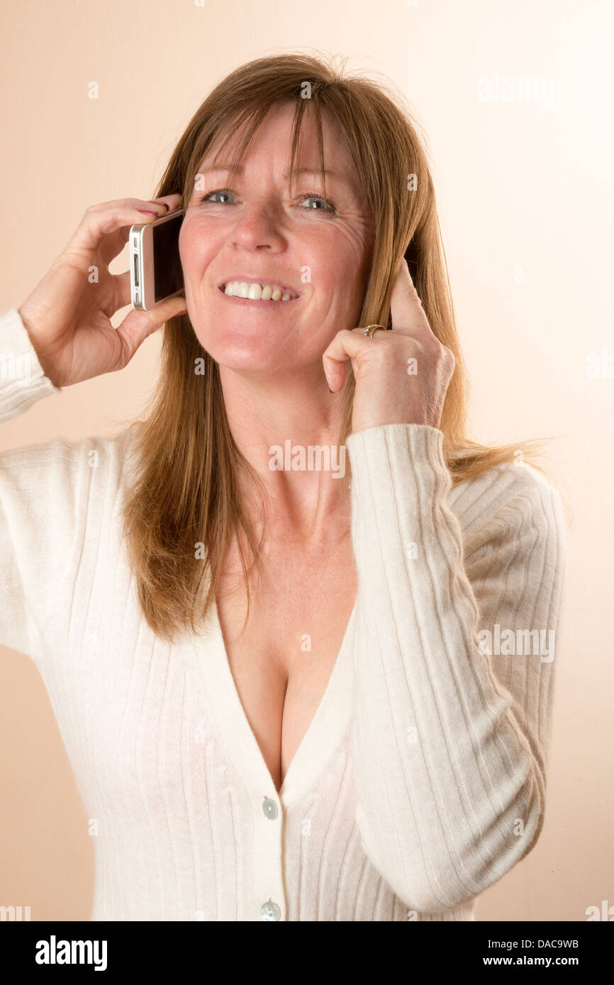 Woman answering a mobile phone call and having difficulty in hearing and has a finger in her ear - Stock Image