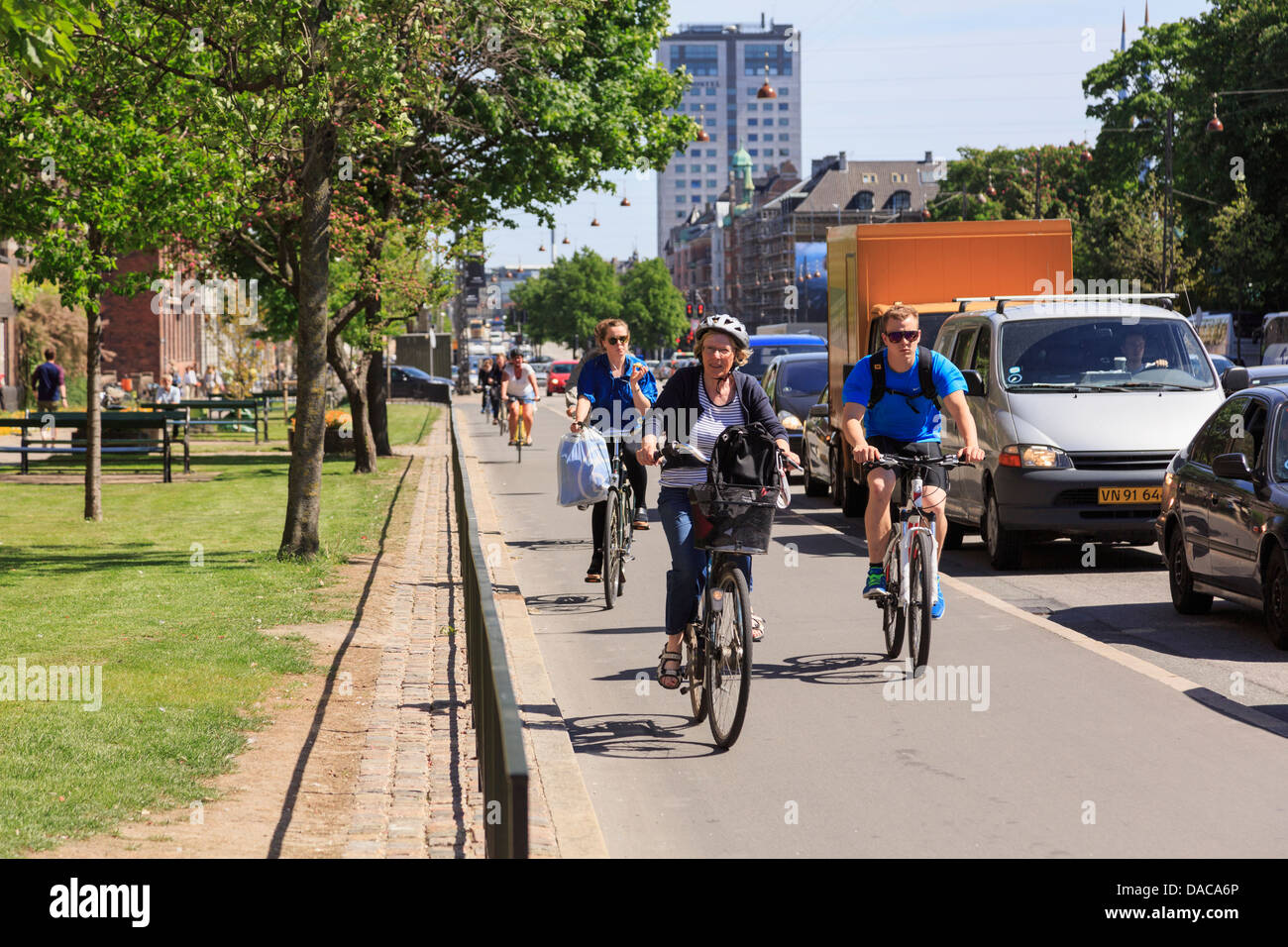 Copenhagen cyclists riding on cycle lane along busy main road in city centre on Hans Christian Andersens Boulevard, - Stock Image