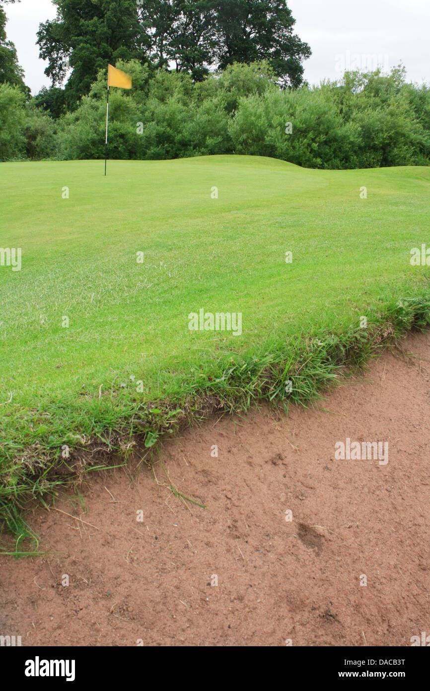 Golf course portrait with the bunker in the foreground the flag on the green a general golfing scene with no people - Stock Image