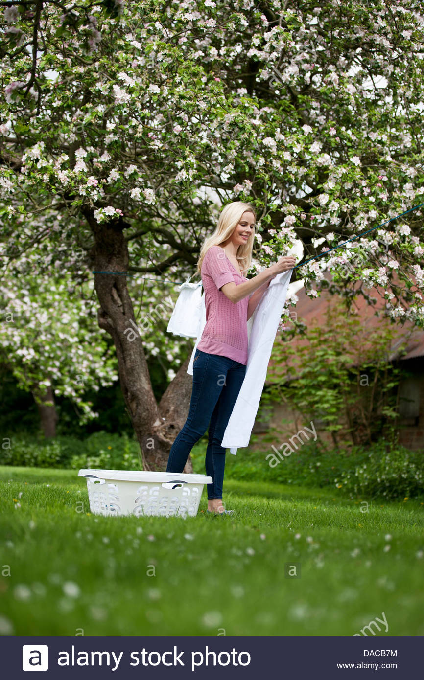 A young woman hanging out washing in springtime - Stock Image