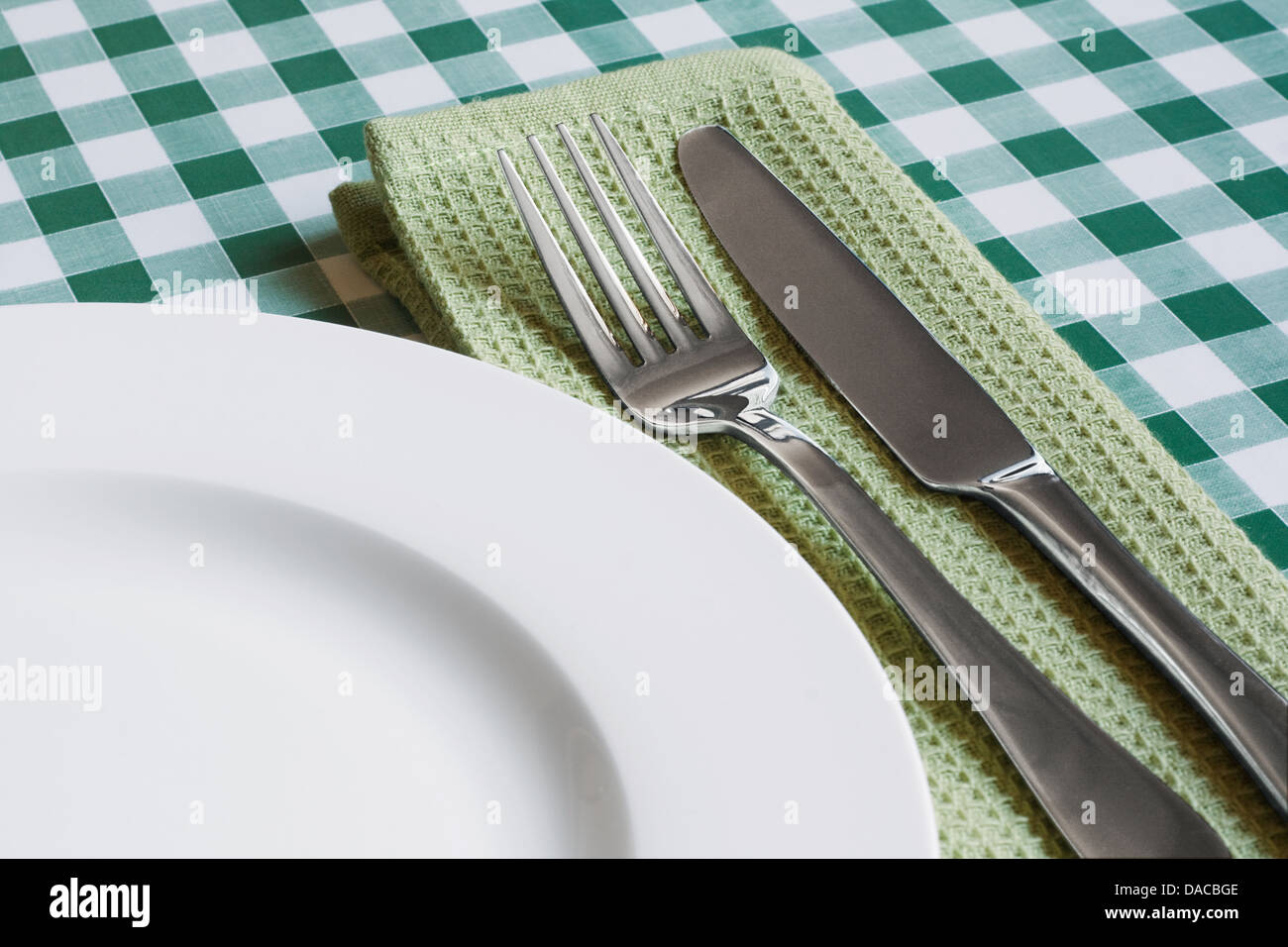 place setting with empty plate, knife and fork on a green gingham background popular symbol for diners and cafes - Stock Image