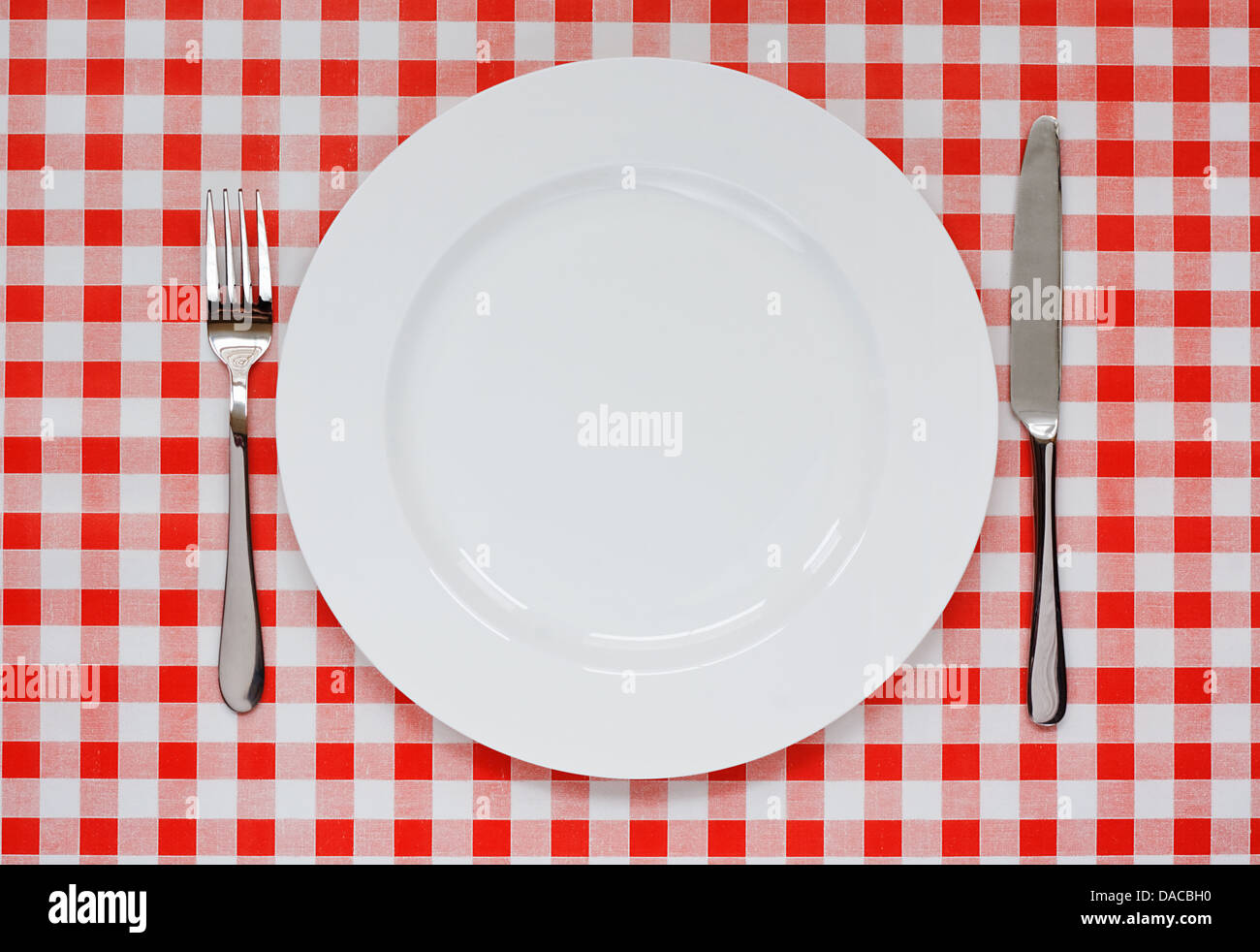Empty plate setting with plate, knife and fork on red gingham background popular symbol for diners and cafes - Stock Image