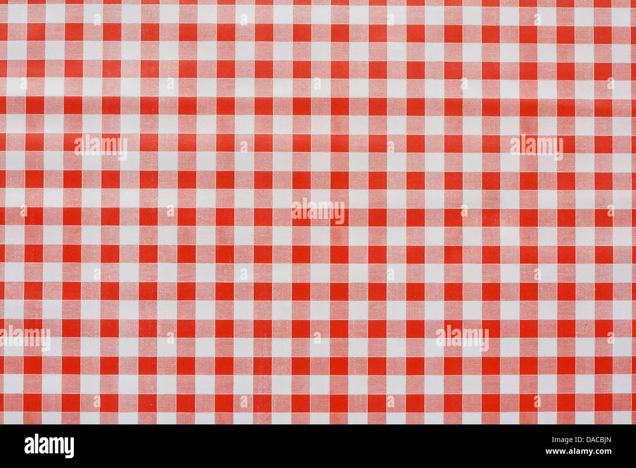 Red gingham tablecloth often found in diners and cafes a popular traditional covering for tables where food is consumed - Stock Image