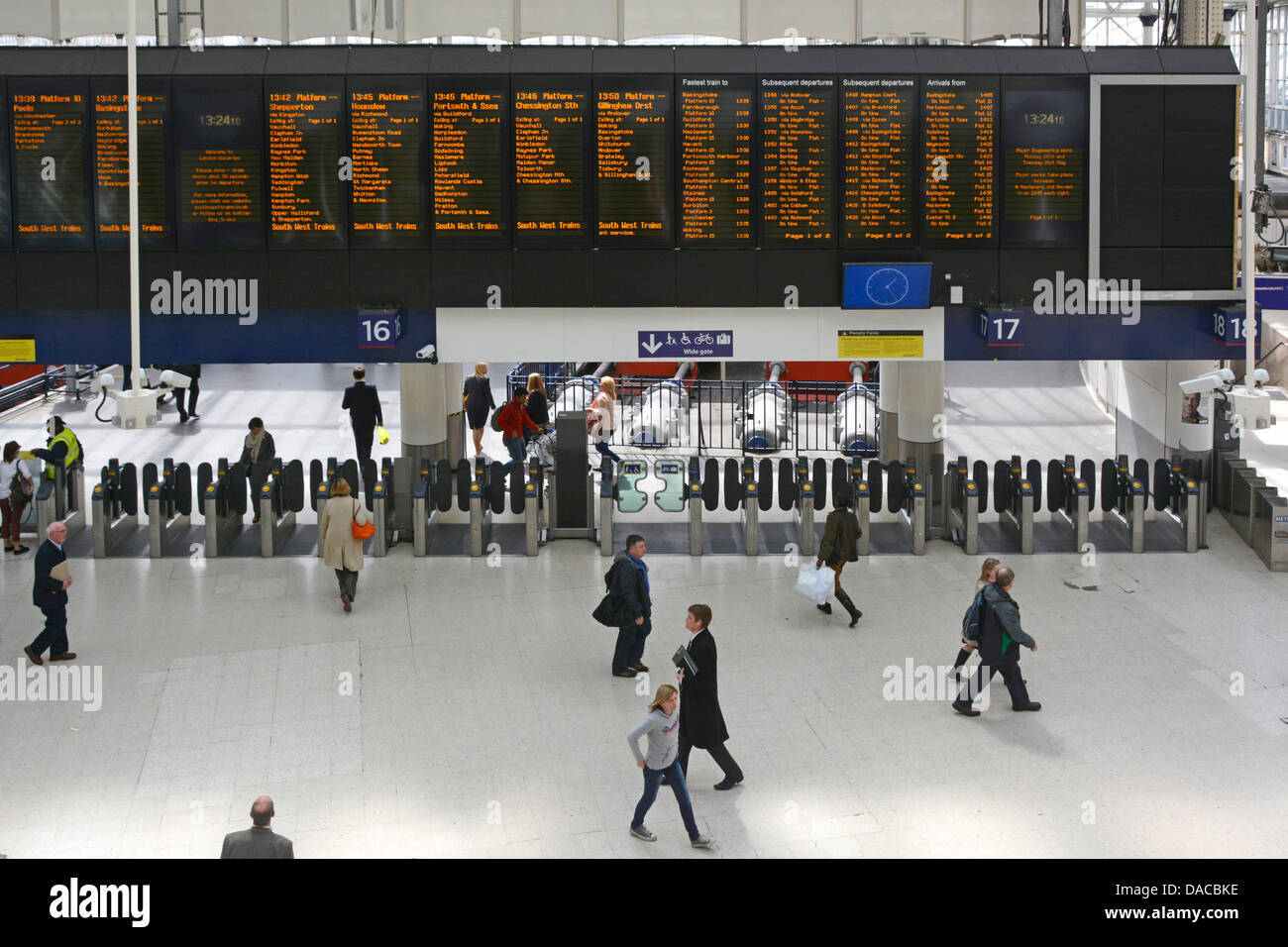 Waterloo railway station arrival and departure information panels above automated ticket barriers - Stock Image