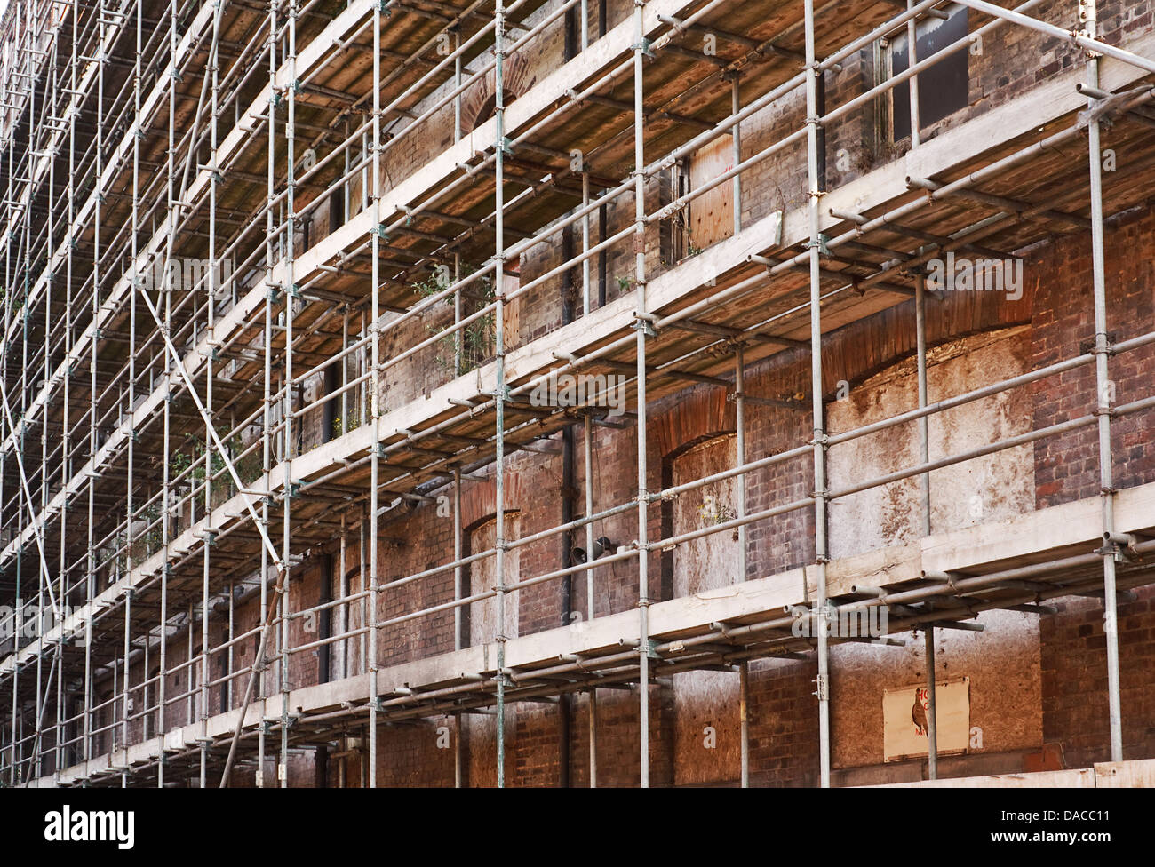 Scaffolding supporting an old derelict building - Stock Image