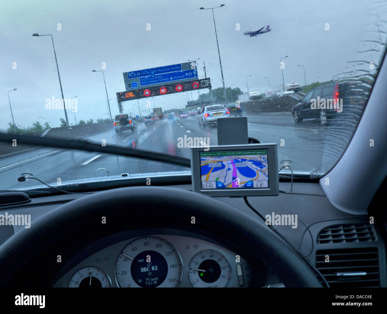 M25 Orbital at Heathrow airport in rain conditions with aircraft on final approach red speed hazard lights on information - Stock Image