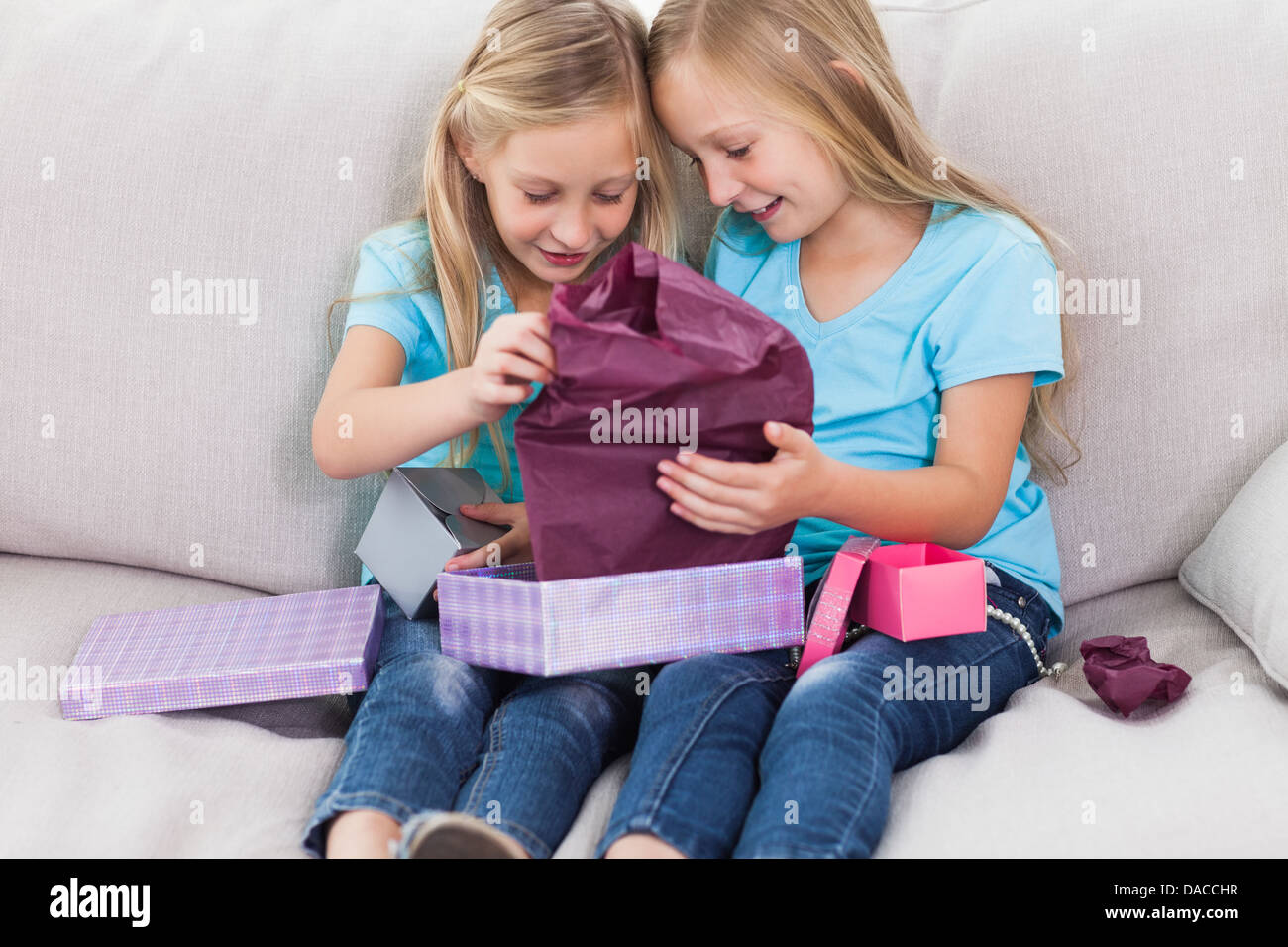 Young Twins Unwrapping Birthday Gift Sitting On A Couch