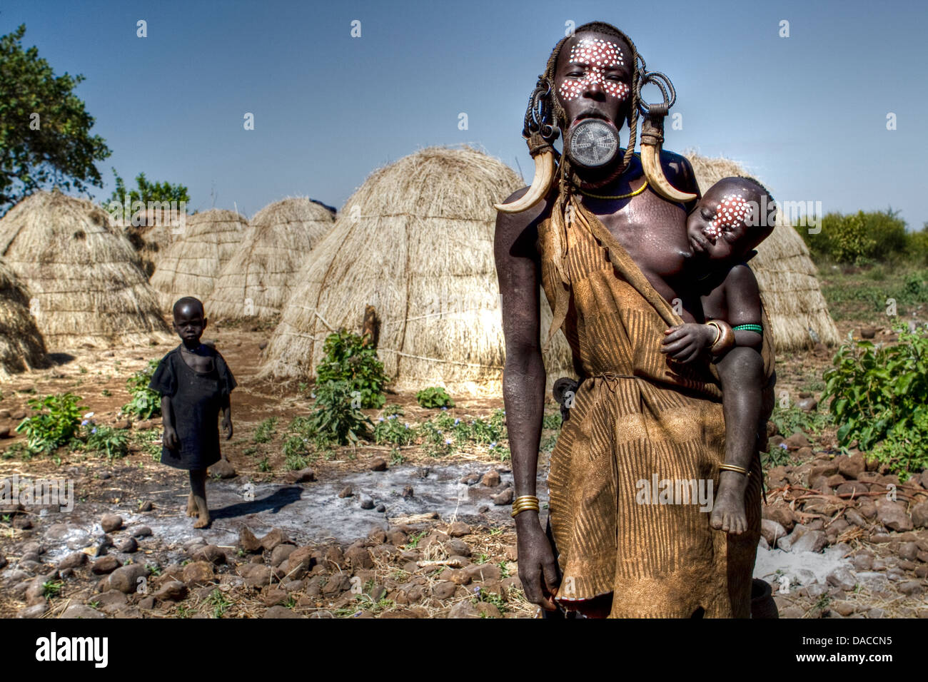 Mursi woman wearing clay disc in lower lips and her child in a village in southern Ethiopia - Stock Image