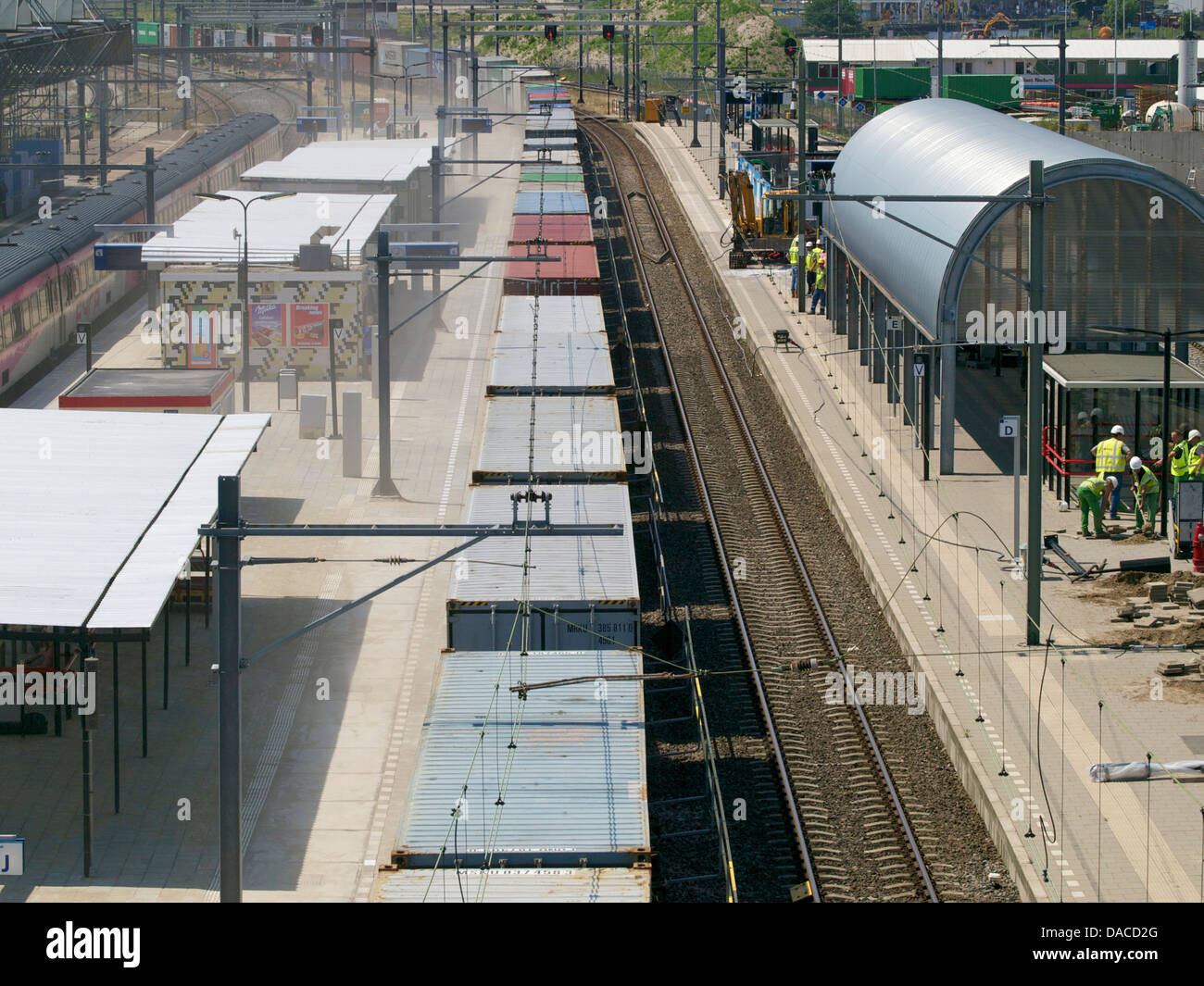 Very long freight train carrying containers going through station Breda, the Netherlands - Stock Image