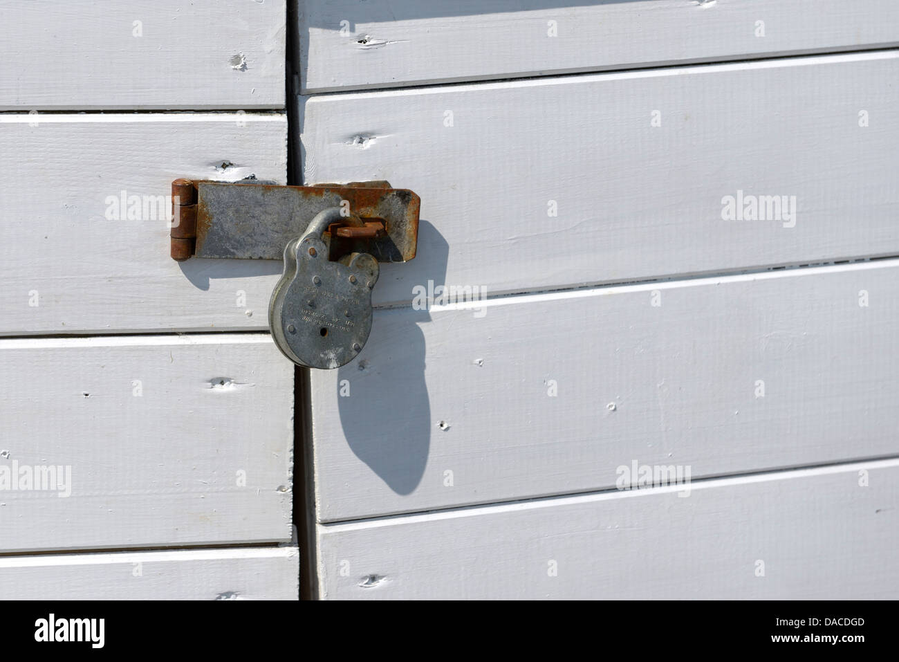 A henry squire padlock attached to a hasp and staple to keep some doors closed - Stock Image
