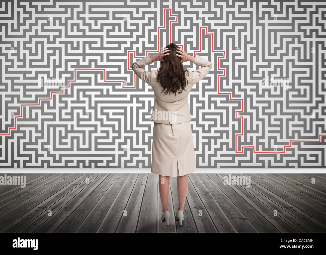 Puzzled businesswoman looking at a maze - Stock Image