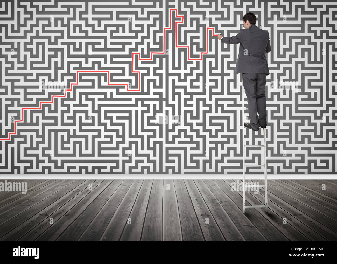 Businessman standing on a ladder solving maze puzzle - Stock Image