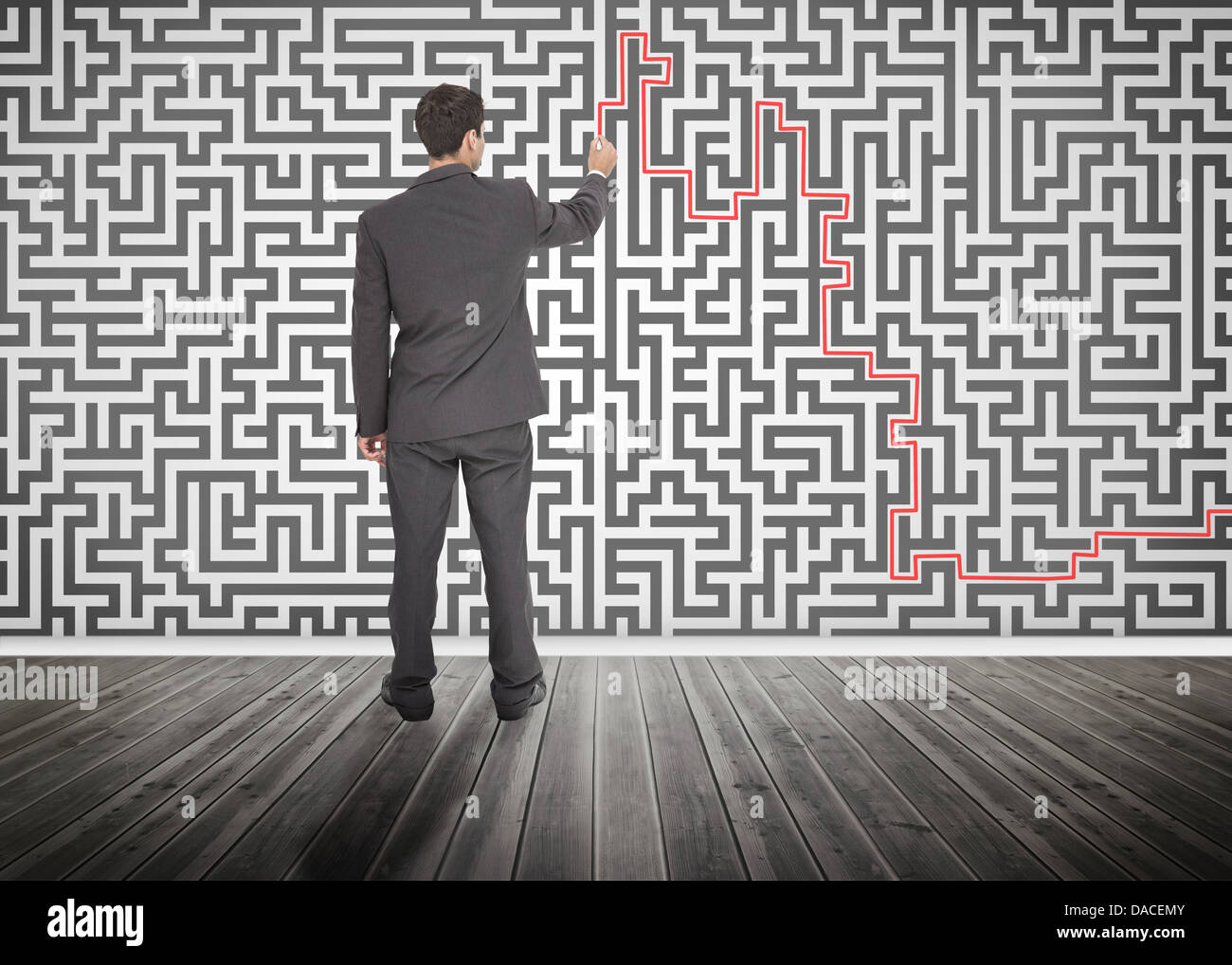 Businessman tracing a red line on a maze - Stock Image