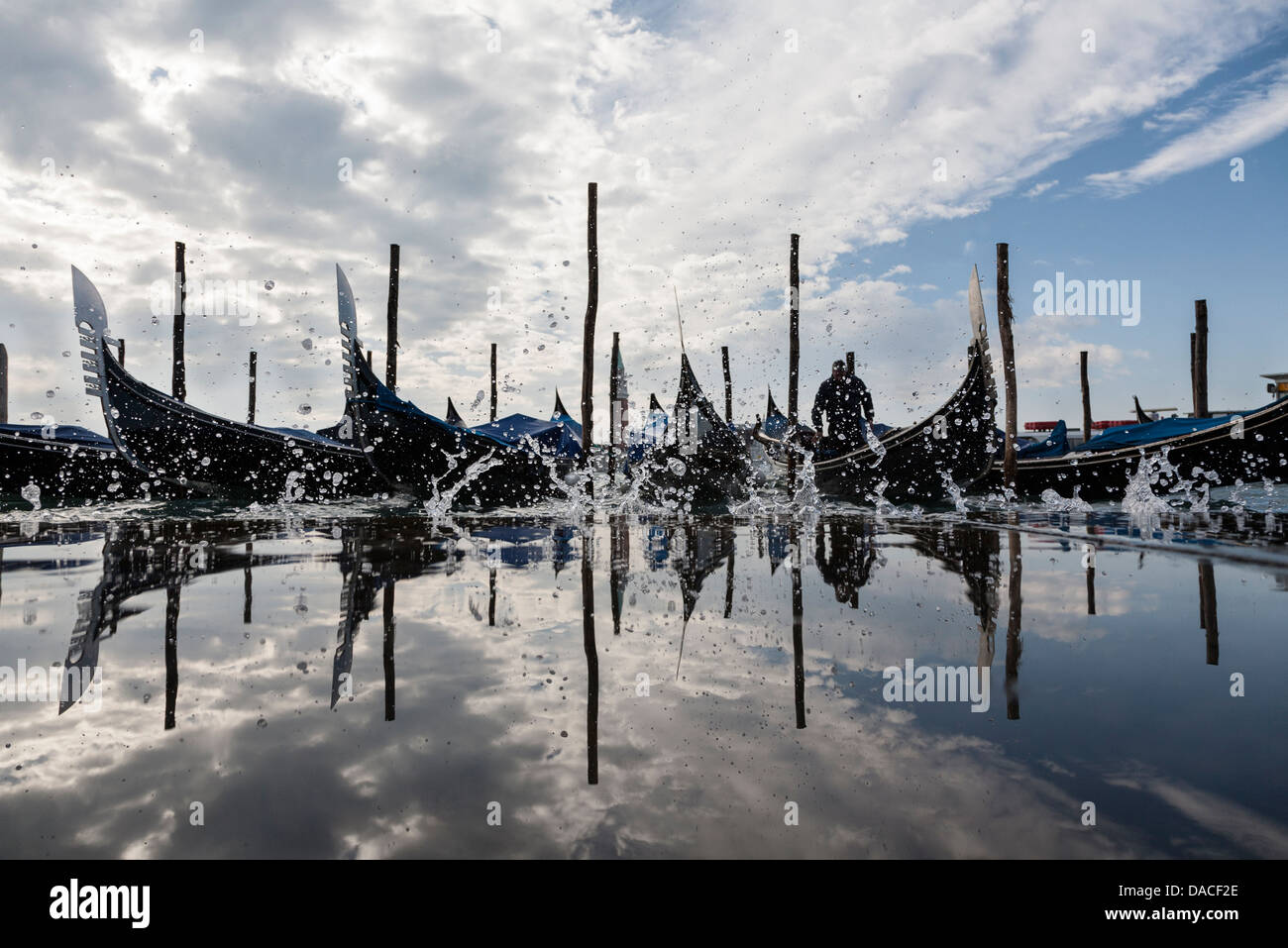 Gondolas with reflection and water splash, Venice, Italy Stock Photo