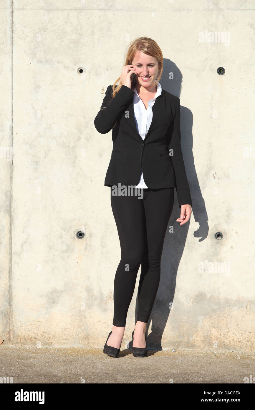 Businesswoman talking on the phone leaning on a concrete wall - Stock Image